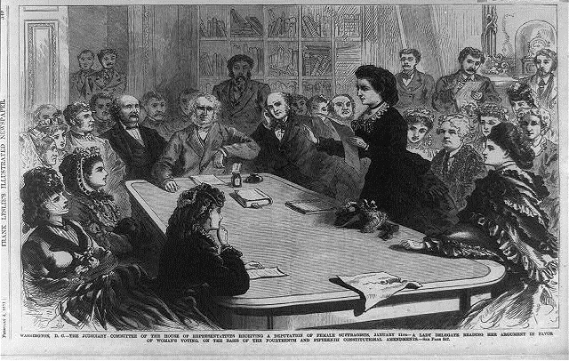 House of Representatives committee receiving a delegate reading her argument in favor of woman's voting, on the basis of the 14th and 15th Amendments, Library of Congress.