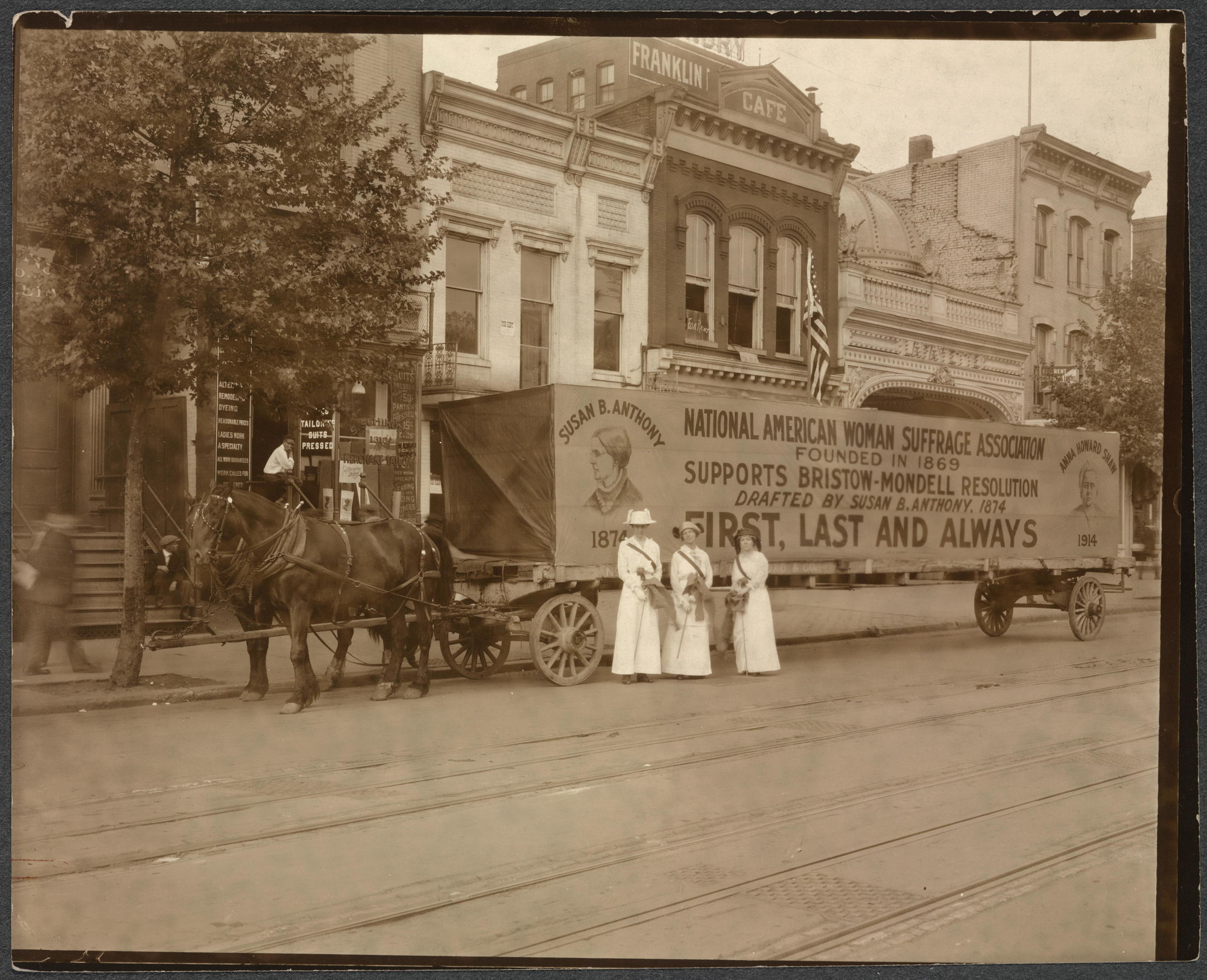Three women stand in front of a horse-drawn wagon with a sigh supporting the NAWSA, Library of Congress.