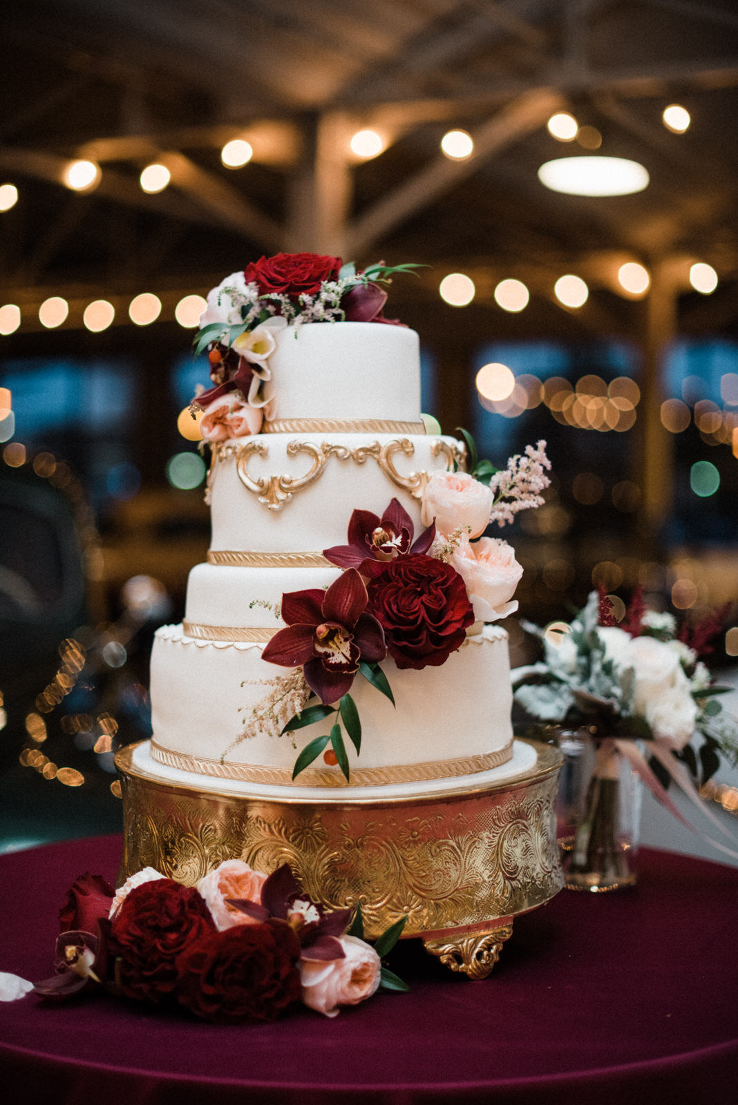 White and gold wedding cake at Americas Packard Museum wedding