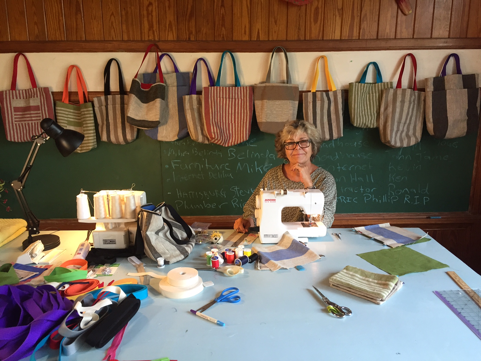 Kate in the studio, back and forth between her sewing machine and serger to make her linen tote bags.