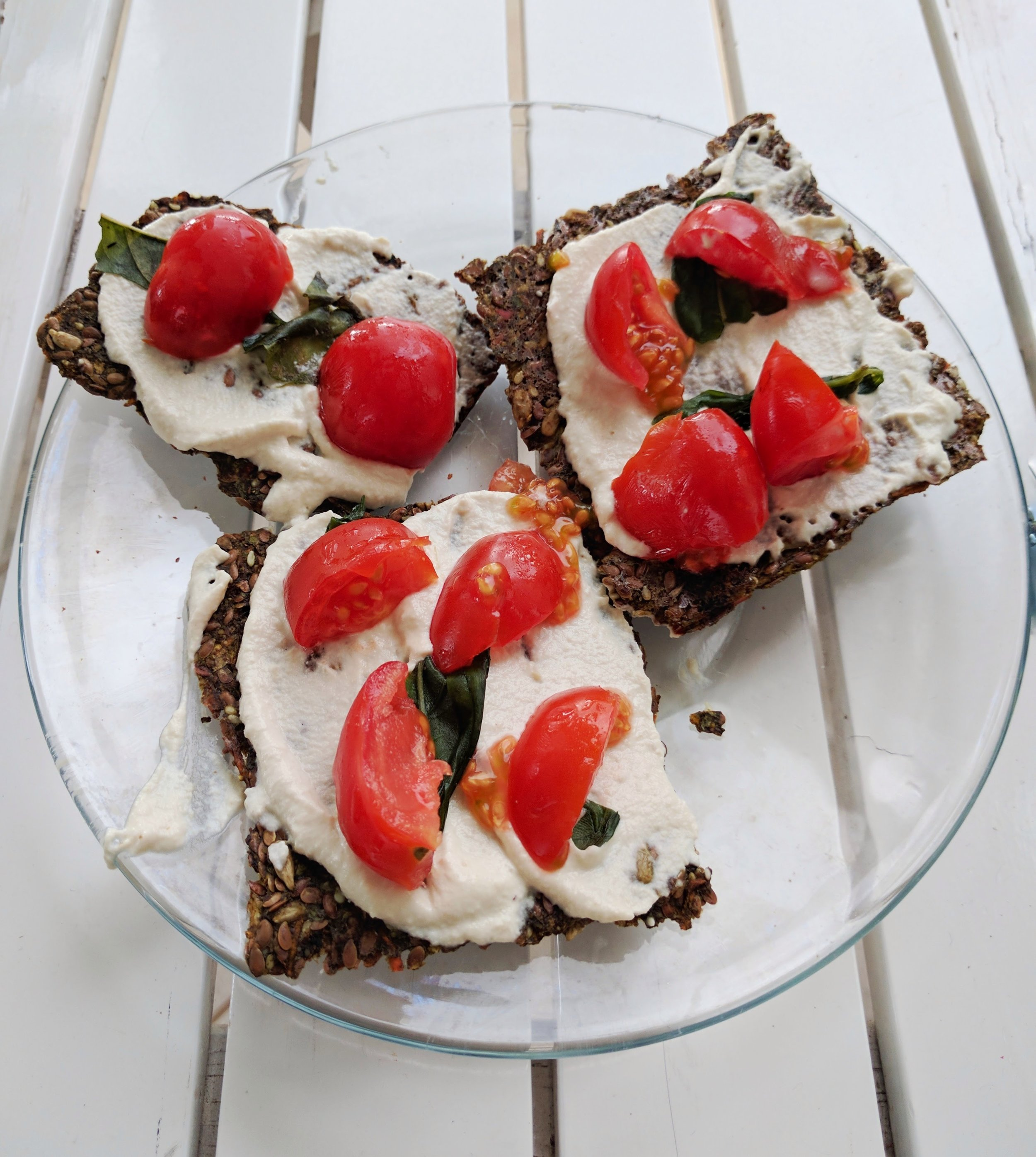 Raw, vegan pizza bites: raw, vegan flax seed crackers topped with cashew cheese, basil and cherry tomatoes.  Costa Rica