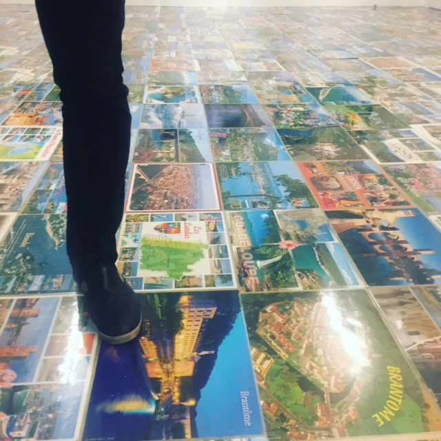 """The foot of a man standing on a floor made of kitsch postcards from France's most iconic touristic spots at the opening of the art show """"Michel Houellebecq: French Bashing"""" on Friday in New York"""