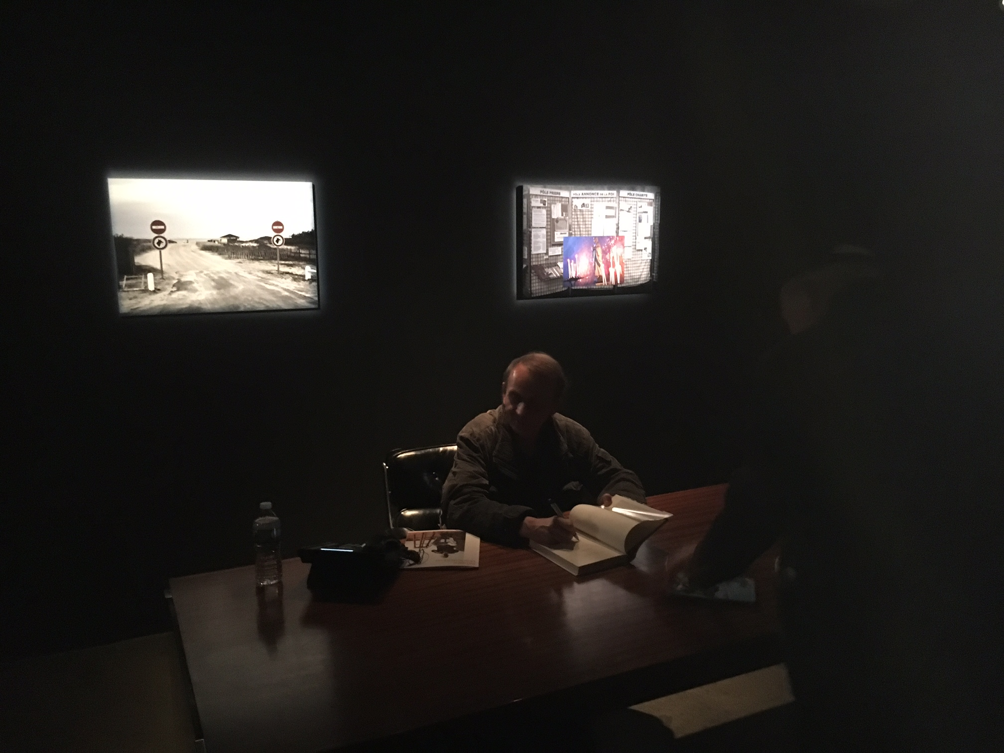 """Novelist, poet, and artist Michel Houellebecq signing copies in the dark at the opening of his show """"Michel Houellebecq: French Bashing"""" on Friday in New York. Photo Credit: Joel Whitney"""