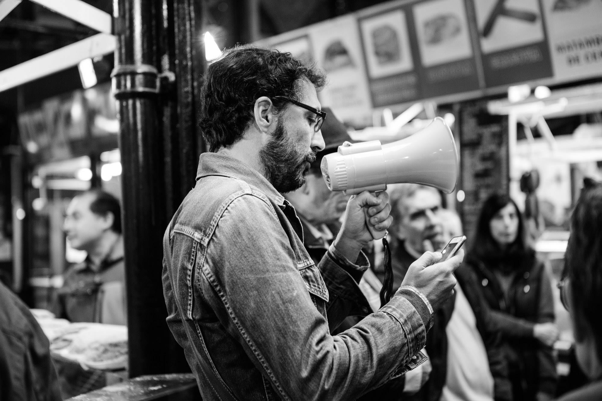 Poet Mariano Rolando Andrade reading aloud some of his verses in popular market Mercado del Progreso on the second day of the FIP International Festival of Poetry of Buenos Aires (June 14-18, 2017). Photo credit: Manuela Uribe