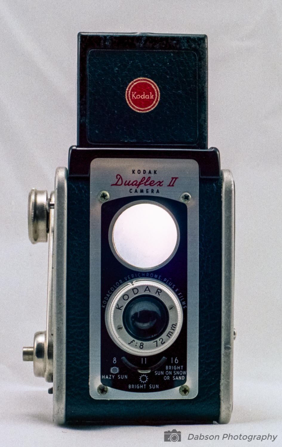 Description - Basically the Duaflex system is a box camera with an expanded view finder.  It does use a separate taking and viewing lens but they are not connected.  The taking lens (bottom) is a zone focus lens.  Focus cannot be seen in the viewfinder.  The viewfinder lens is fixed focus.  It is adjustable from 3.5 feet to Infinity.The taking lens on this model is a KODAR 72mm/f8.  72mm is a fairly standard sized lens for medium format photography.  It equates to roughly 50mm on a 35mm film camera. Aperture on this example of the Duaflex II is adjustable.  Settings include f8, f11 and f16.  The shutter speed is fixed and my research shows the shutter speed to have originally been 1/40 second.  Due to age, shutter speeds on these older cameras may vary.  After working the shutter several times, these cameras must be film tested for the real results to be known.