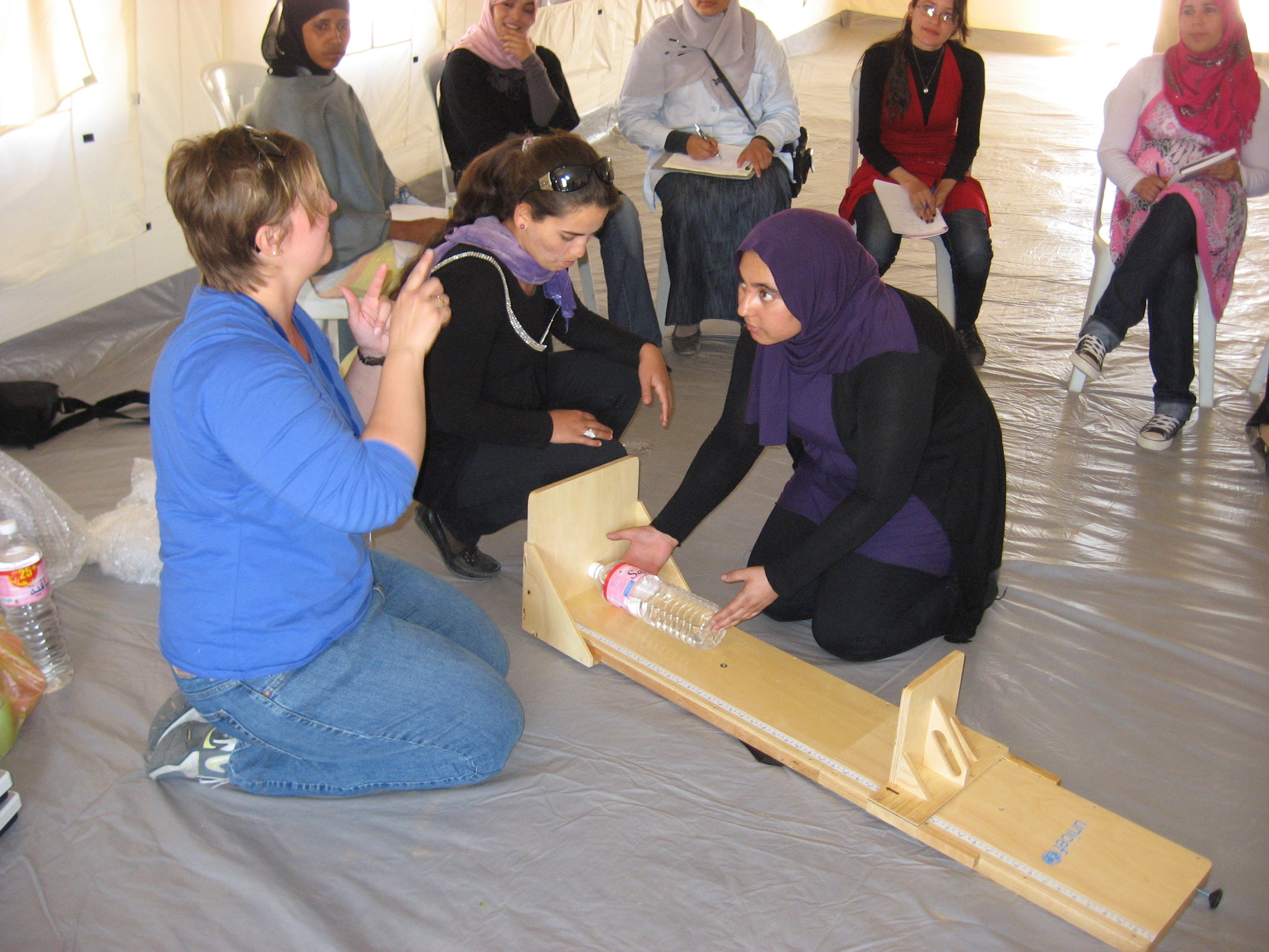 Training staff on how to take a child's height using a water bottle at a refugee camp on the Tunisian border.