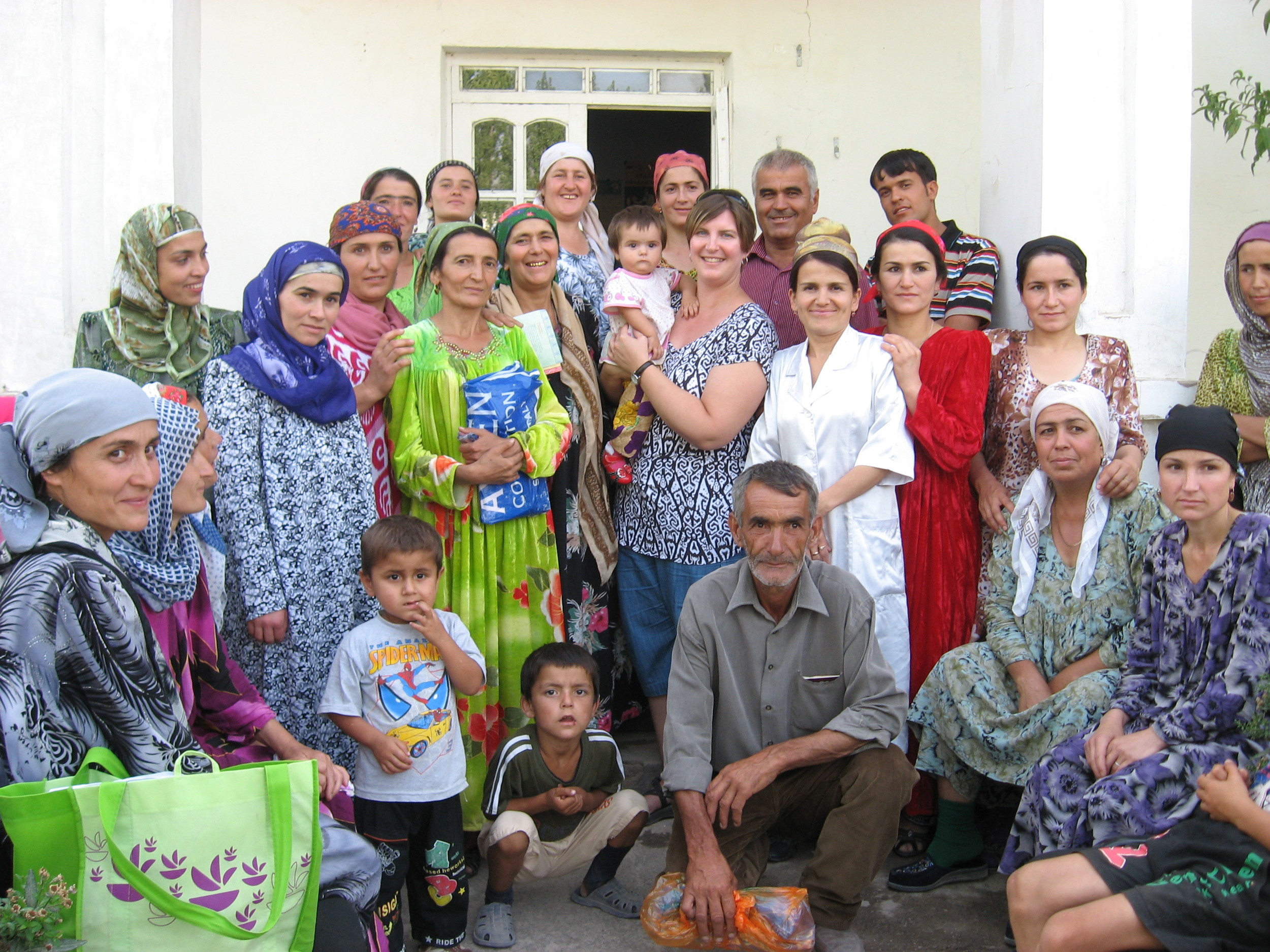 Sonya holding a baby surrounded by a group of Tajik women that participated in a focus group discussion on child health.