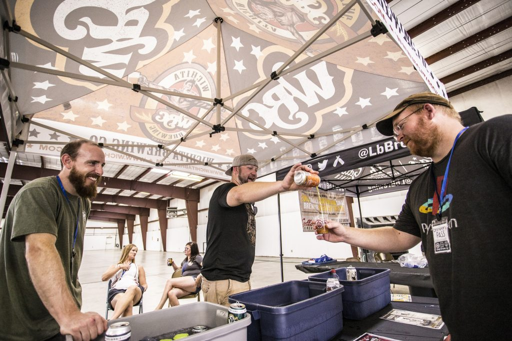 Kyle Banick (center) and Ned Vahsholtz (left) with Wichita Brewing Company provide a sample of their 5:02 Amber Ale to an event-goer at last year's Craft Brew Expo at the Great Bend Expo Complex. (Photo by Brandon Steinert)
