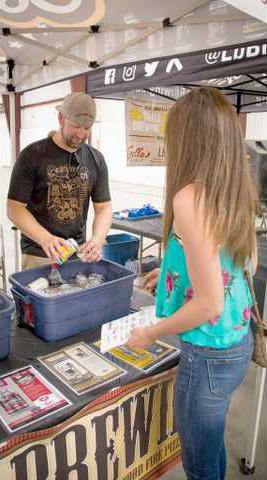 Wichita Brewing Company Operations Manager Kyle Banick pours a beer sample for a Craft Brew Expo attendee at the Great Bend Expo Complex at Bike Brew Q on Saturday, July 29. - photo by COURTESY PHOTO