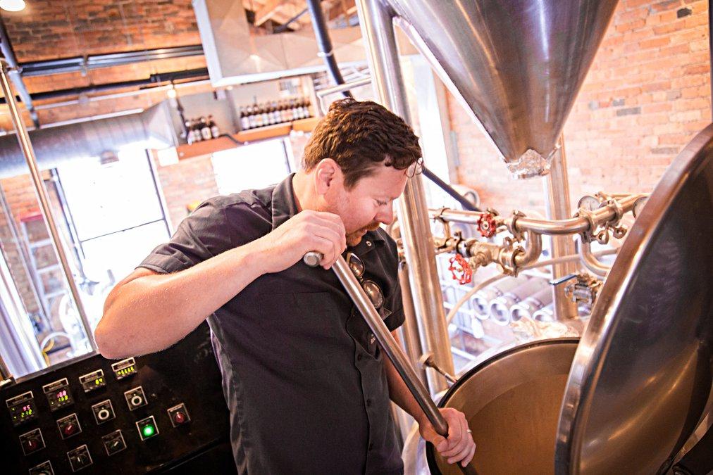 Head Brewer Brendan Arnold stirs the mash at LB Brewing in Hays, KS. - Photo by Joe Viduska