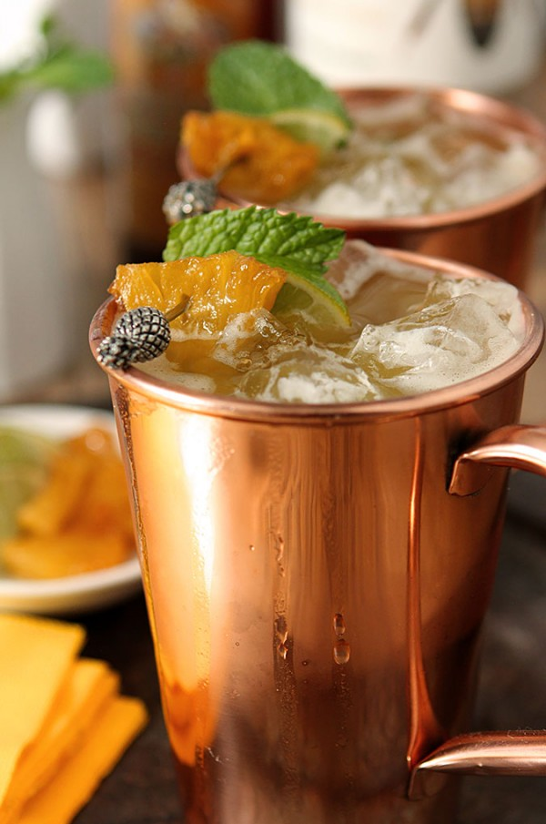BROWN SUGAR AND ROASTED PINEAPPLE MOSCOW MULE  Roasted Pineapple:  1 whole pineapple  1/4 cup brown sugar (use more if necessary)  Cocktail:  2 tbsp roasted pineapple, chopped in 1/2-inch pieces  3–4 mint leaves  2 oz vodka  1 oz pineapple juice  Juice of 1 lime  2–3 oz ginger beer  Garnish: Mint sprig, lime wedges, roasted pineapple wedges  To Roast the Pineapple:  Preheat oven to 450° F. Peel, core, quarter and slice pineapple into ½-inch wedges. Place the pineapple on a baking sheet and sprinkle with the brown sugar. Roast for 10 minutes. Remove pineapple from oven, turn the pieces over, and sprinkle with more brown sugar. Roast for another 10 minutes. Remove from the baking sheet to either waxed paper or parchment, and let cool completely. Dice half of the pineapple and leave the other half for a garnish (minus the pieces I just know you will eat!)   To Make the Cocktail:  Combine the diced roasted pineapple and mint leaves in the bottom of a cocktail shaker and muddle. Add the vodka, pineapple juice and juice of one lime and stir. Fill the shaker with ice and shake until cold. Fill two glasses with ice, and pour the mixture over the ice. Top with the ginger beer, stir gently, and garnish with a sprig of mint, slice of lime and a wedge of roasted pineapple.