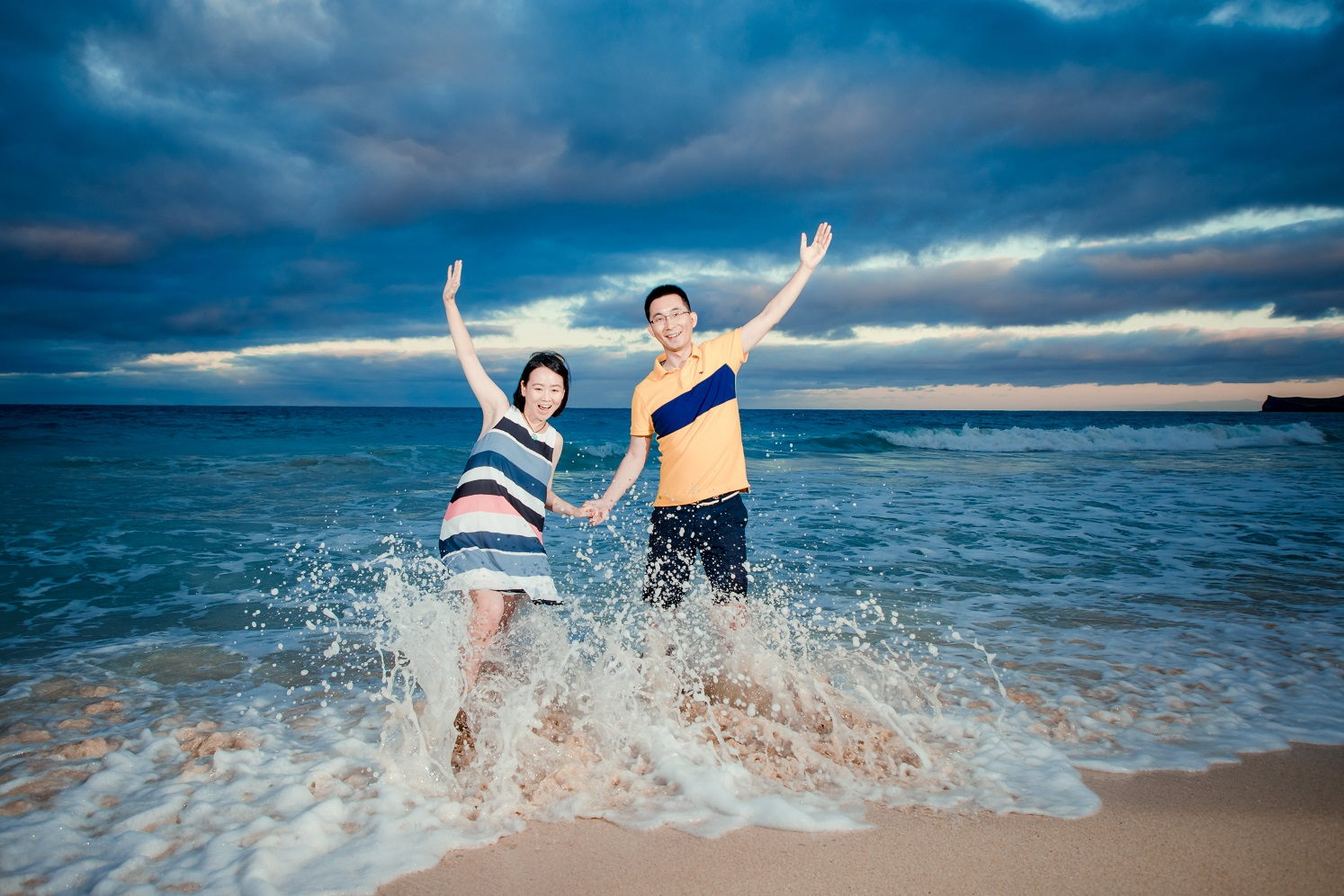 couples engagement portrait in the waves