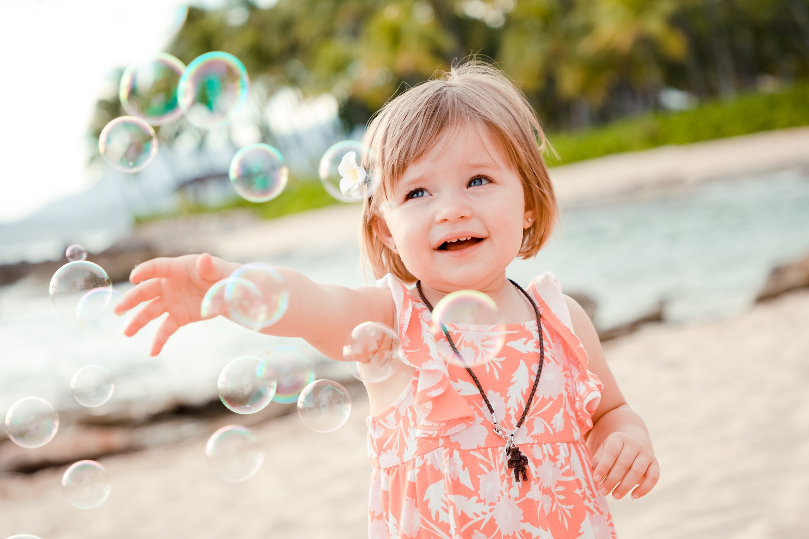 young child catching bubbles on beach in oahu