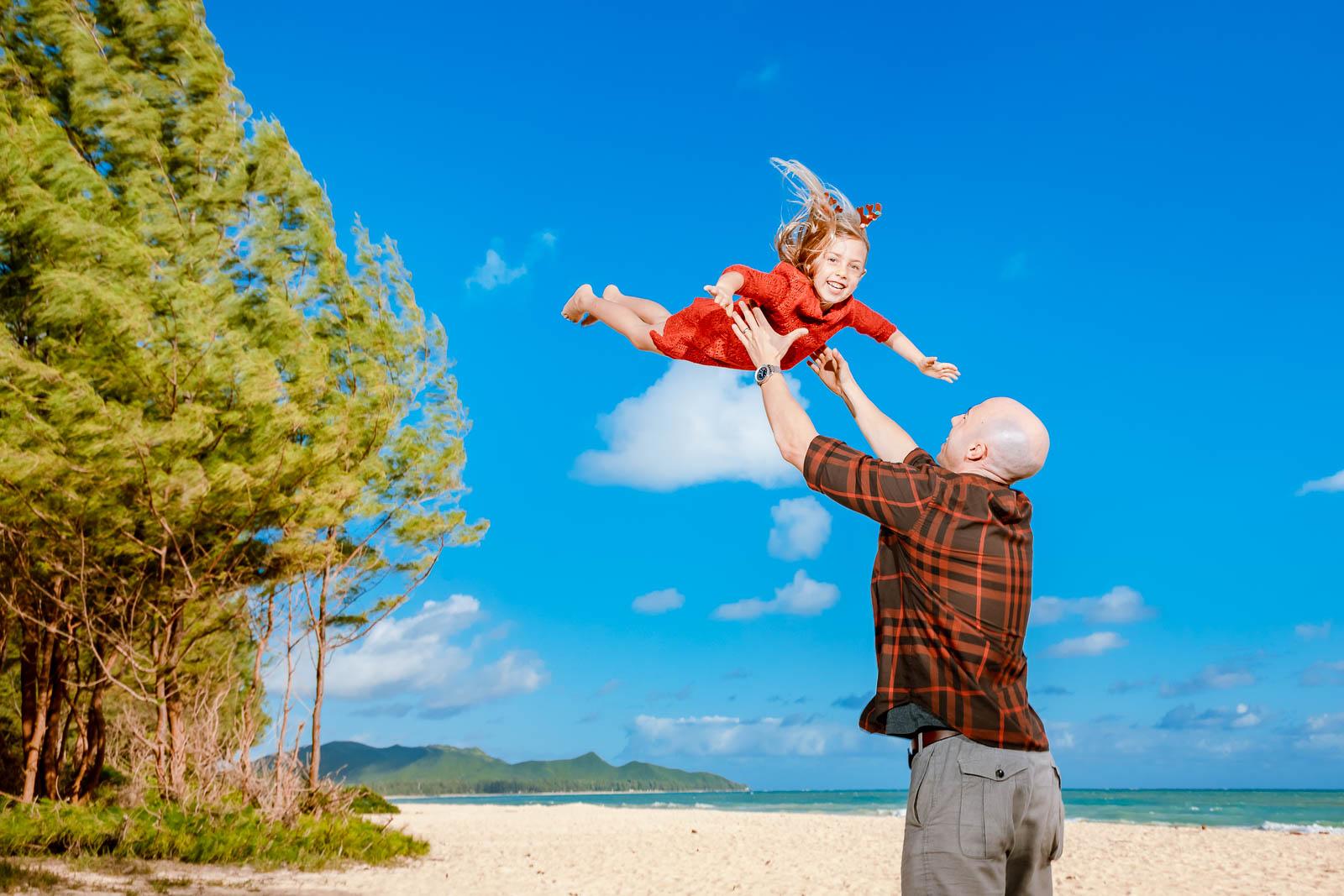 dad tossing kid in sky flying beach ocean oahu hawaii family photo