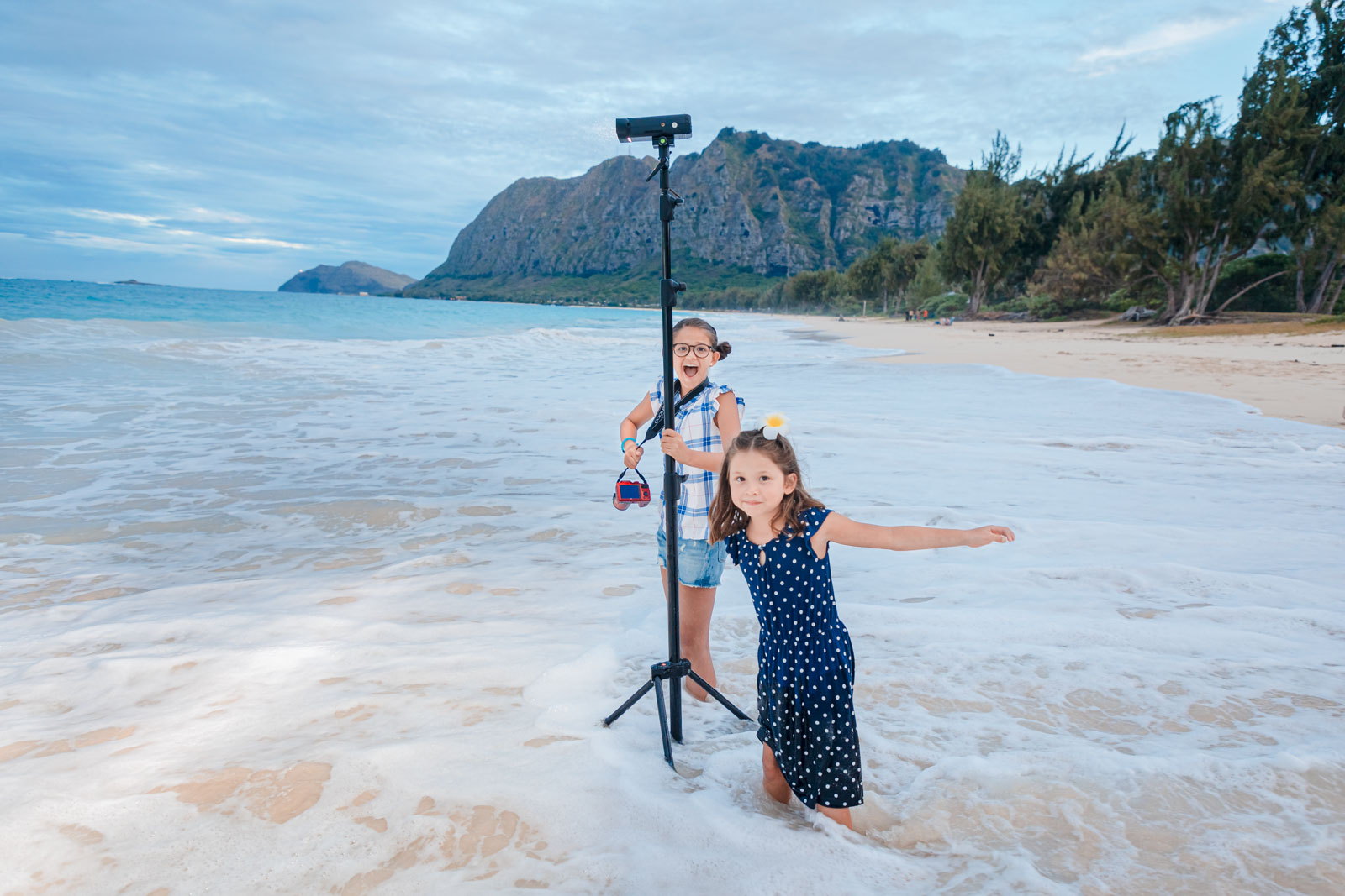 two kids girls during family beach photo session sunset oahu hawaii in ocean