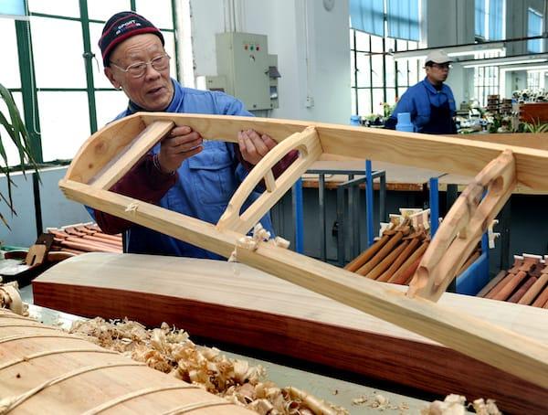 Xú Zhèngāo in 2016, inspecting a guzheng frame. From  qianlong.com