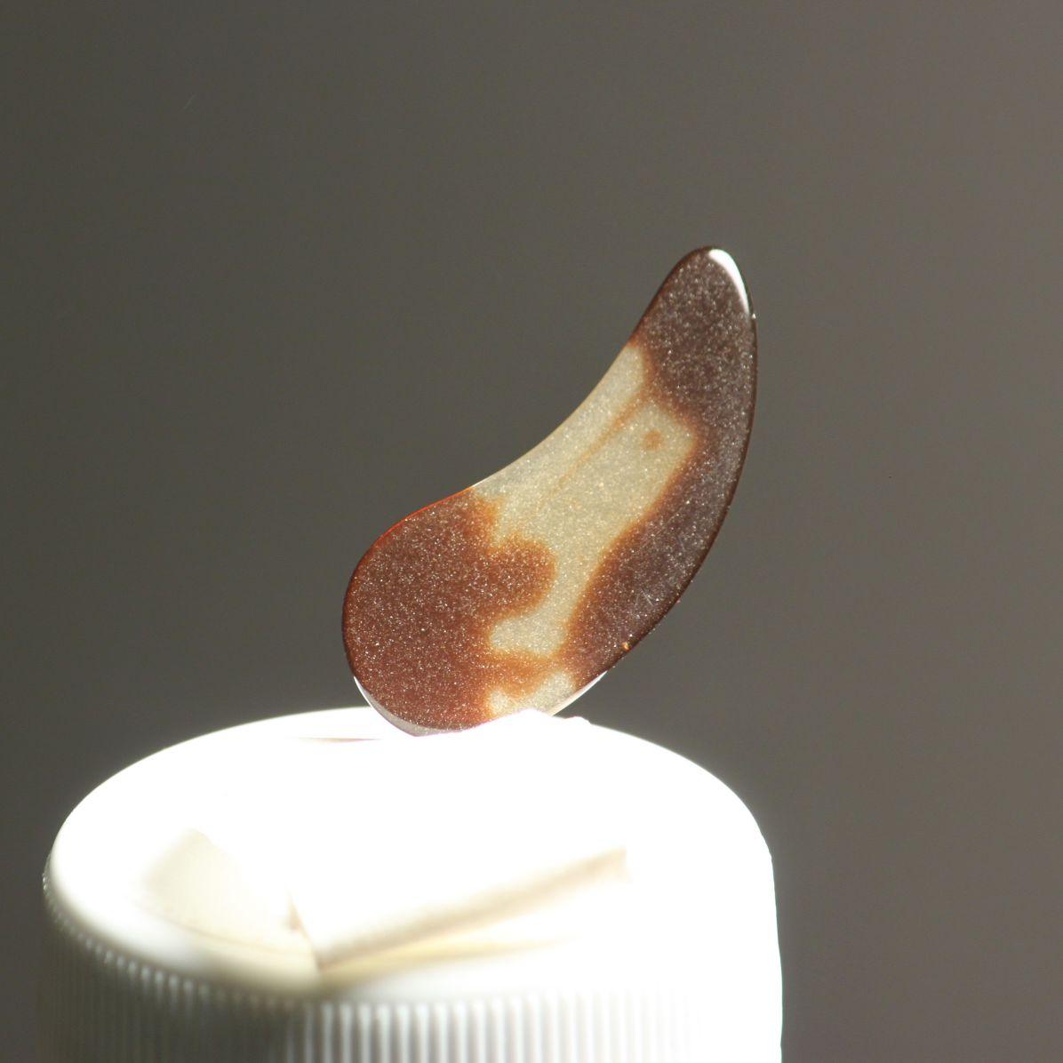 Manmade guzheng nail lit by 200W bulb to reveal microcracks.