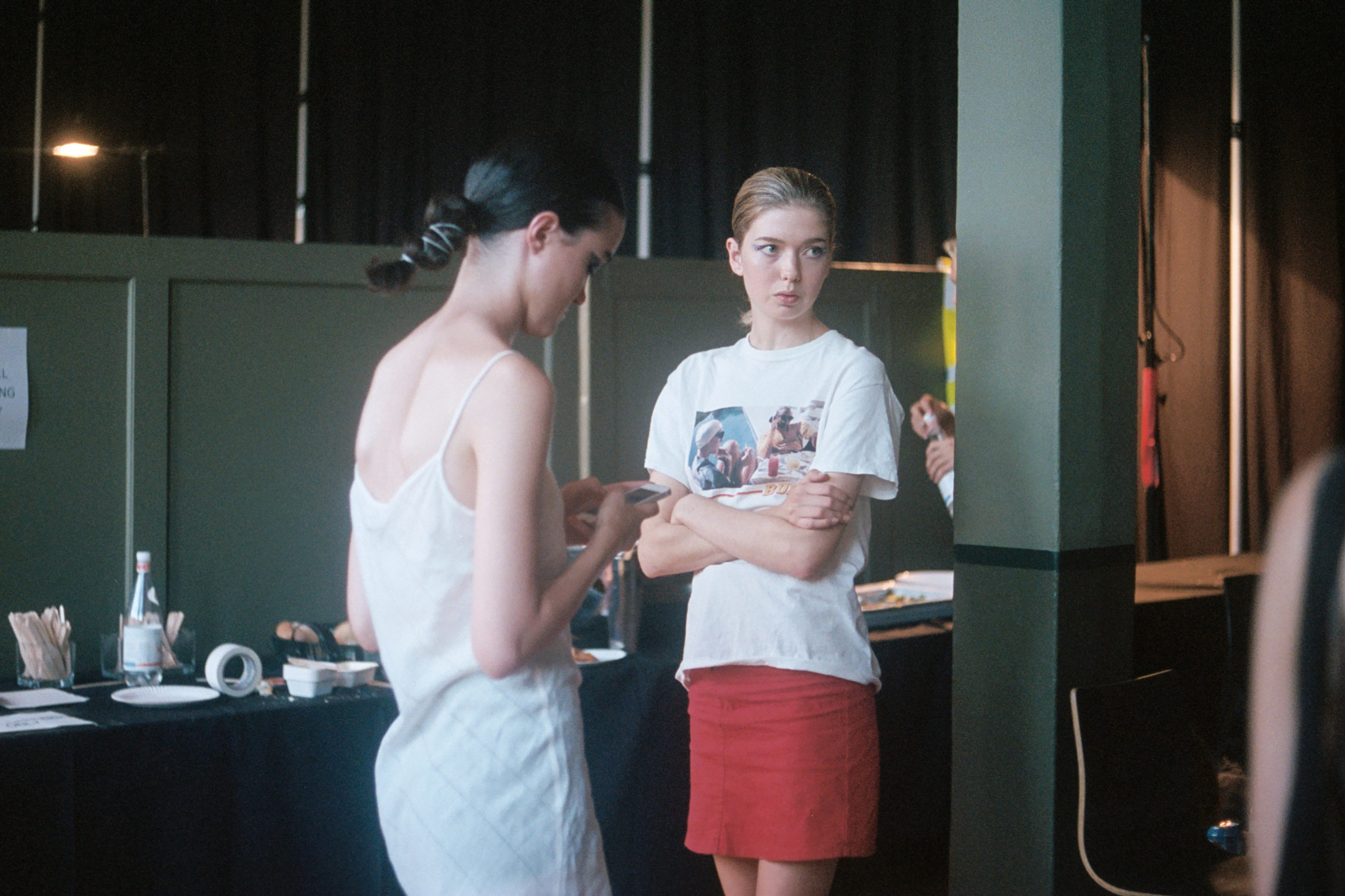 Two models wait post hair and make up for the runway to begin.