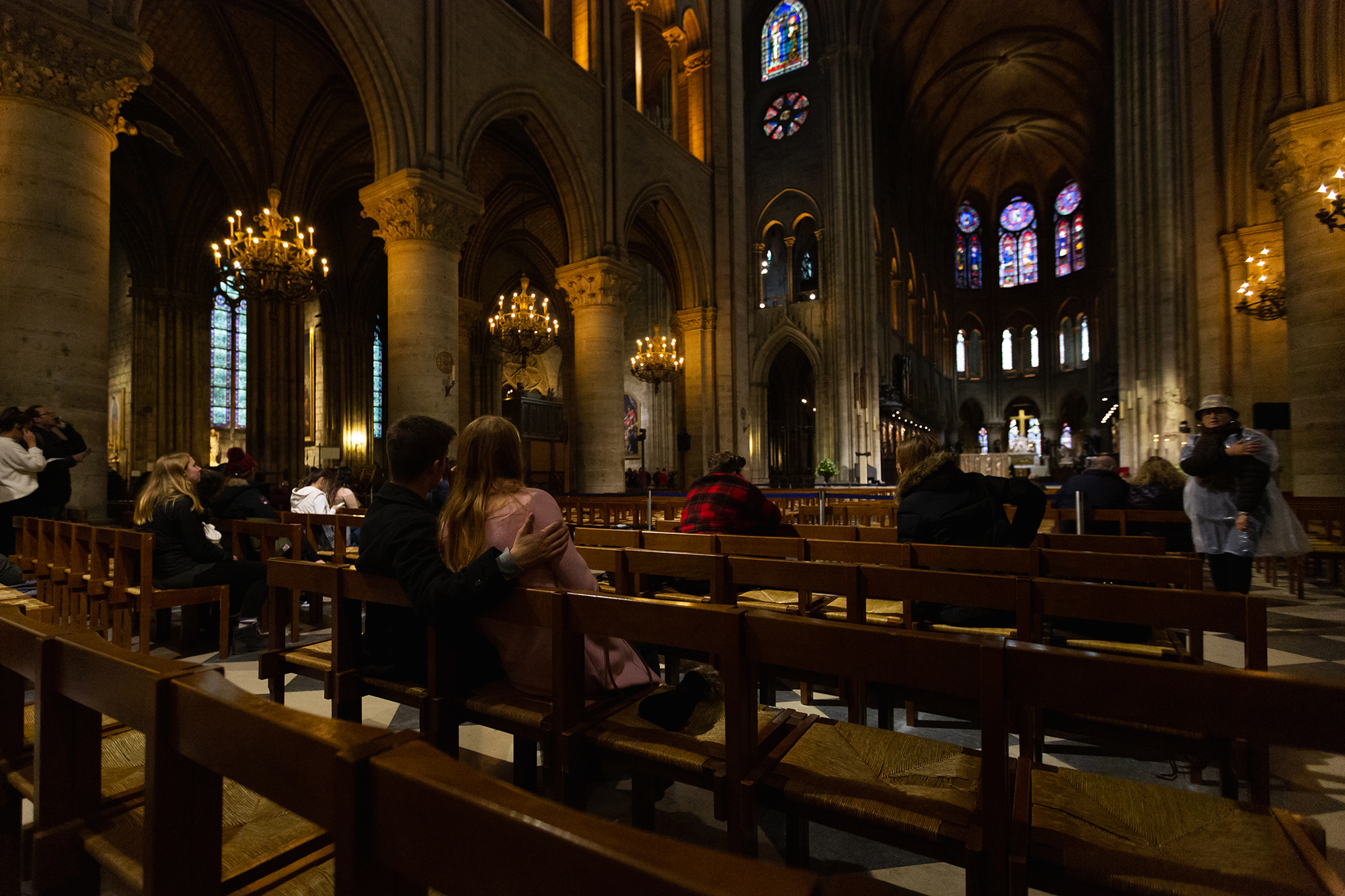 A young couple embraces as they admire the interior of Notre Dame.