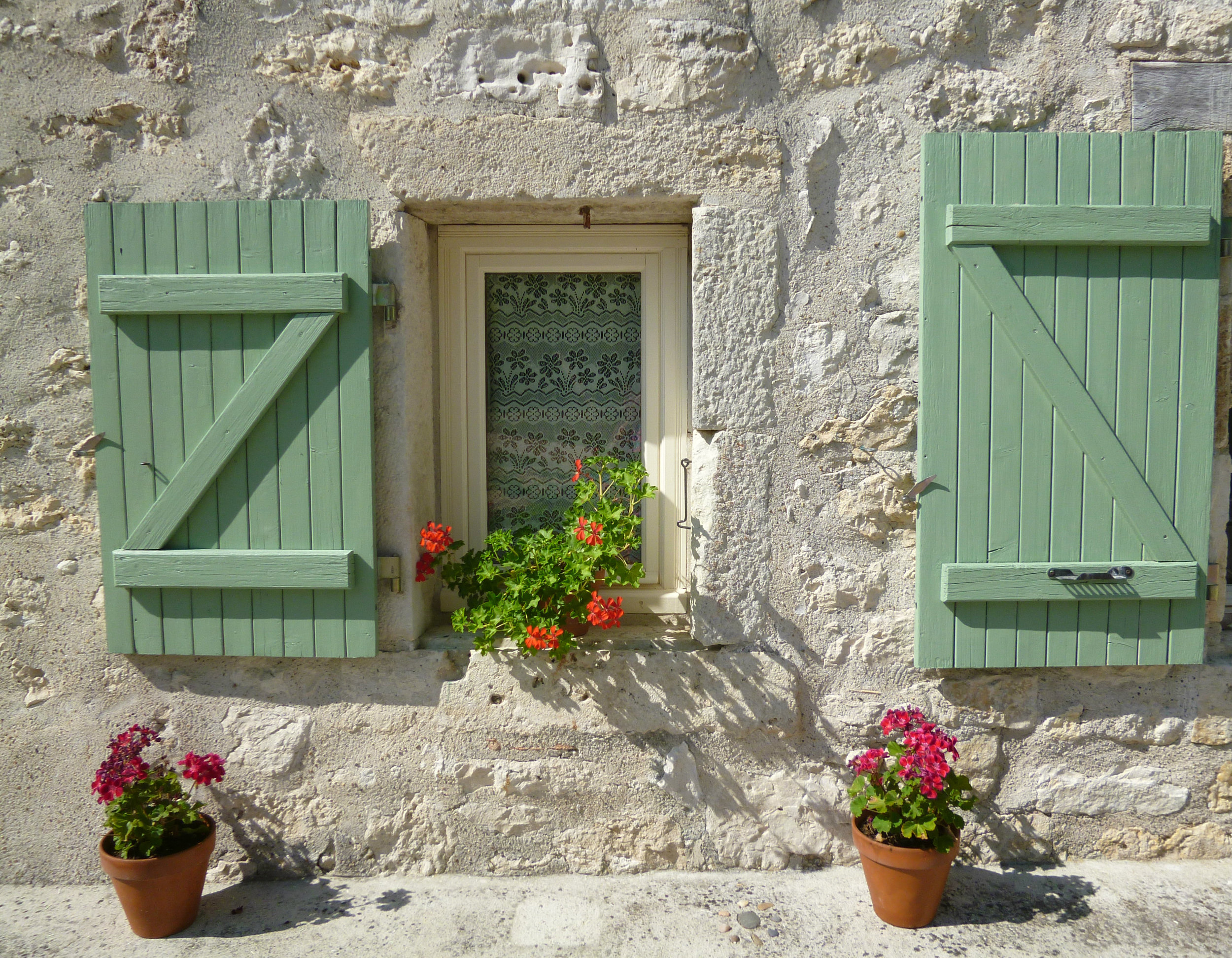 The green shutters supported (photographically) by the geraniums.