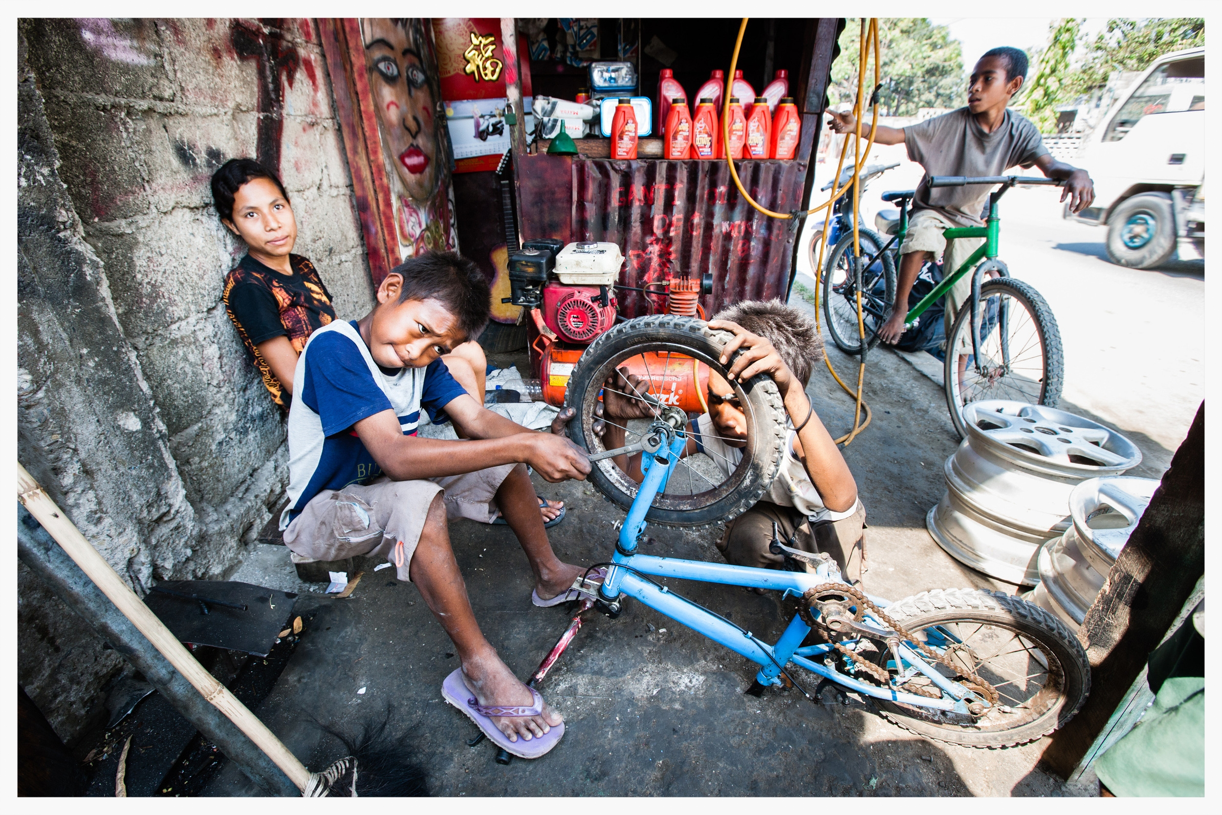 A group of boys run a tyre repair shop, missing out on school.East Timor.Photo: © Marcus Perkins