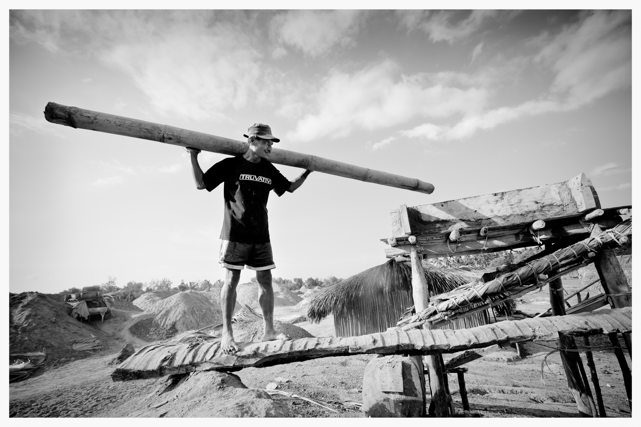 A salt-worker uses a bamboo tube to carry seawater to a clay filter.East Timor.Photo: © Marcus Perkins