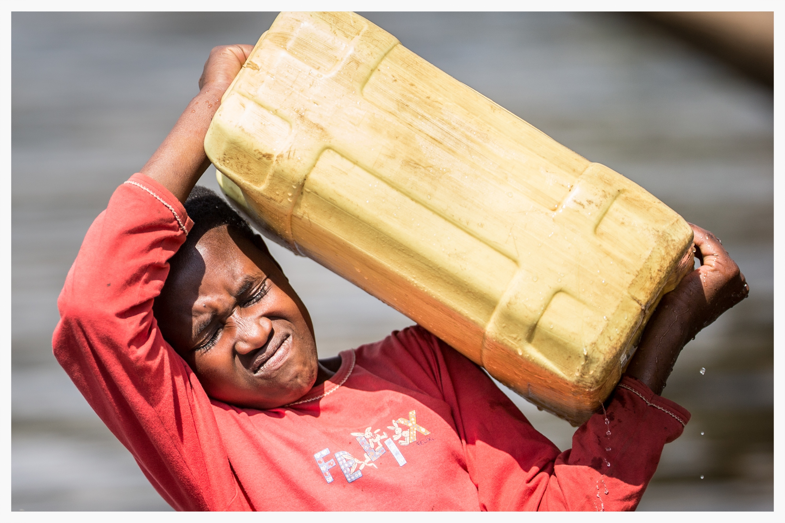 Lifting 20 litres of water (20kg) is tough for an 11-year-old girl. Photo © Marcus Perkins