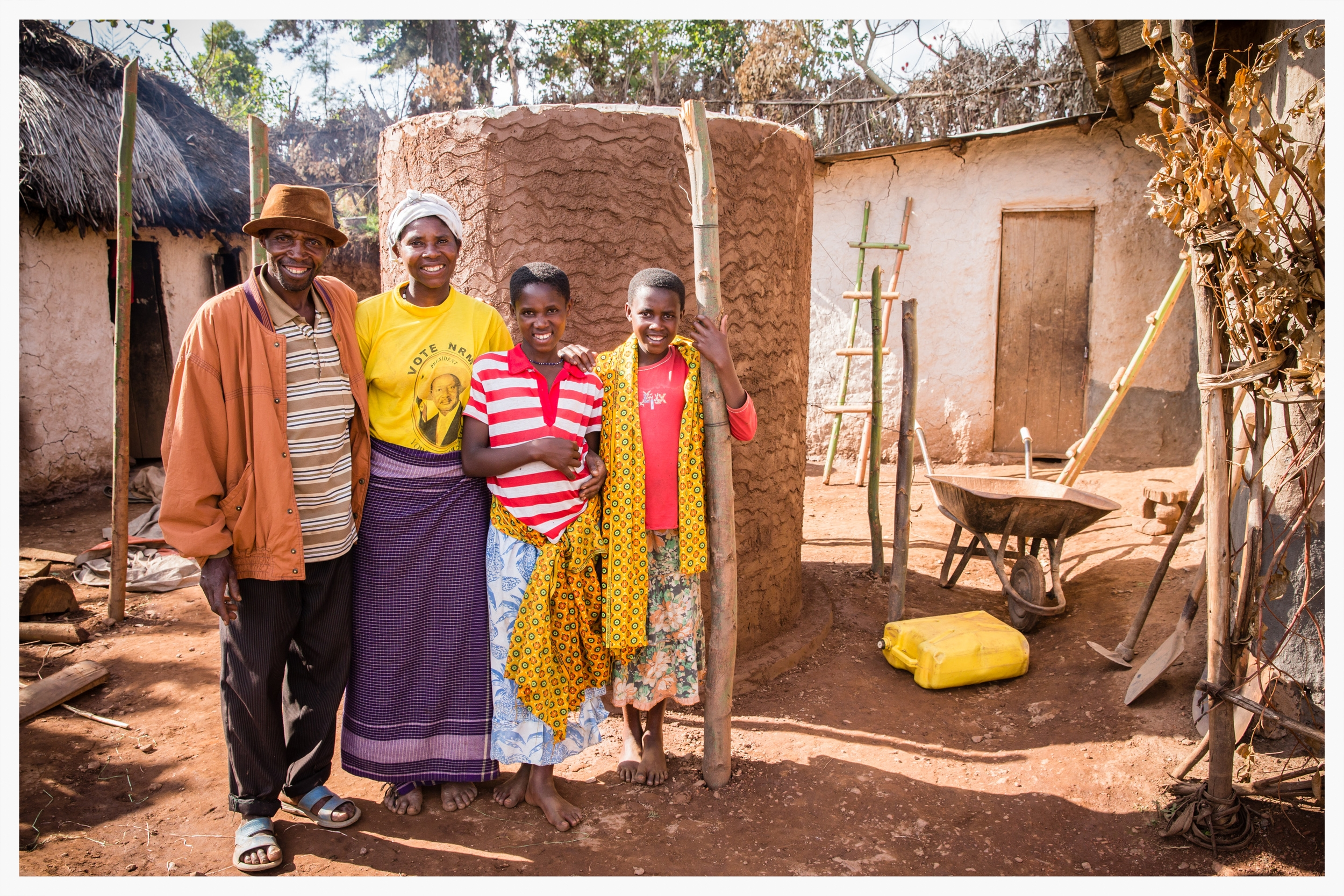 Milton and his family stand next to their water tank which will harvest rainwater from the roof of their home. Rwanyana village, south west Uganda. Photo © Marcus Perkins