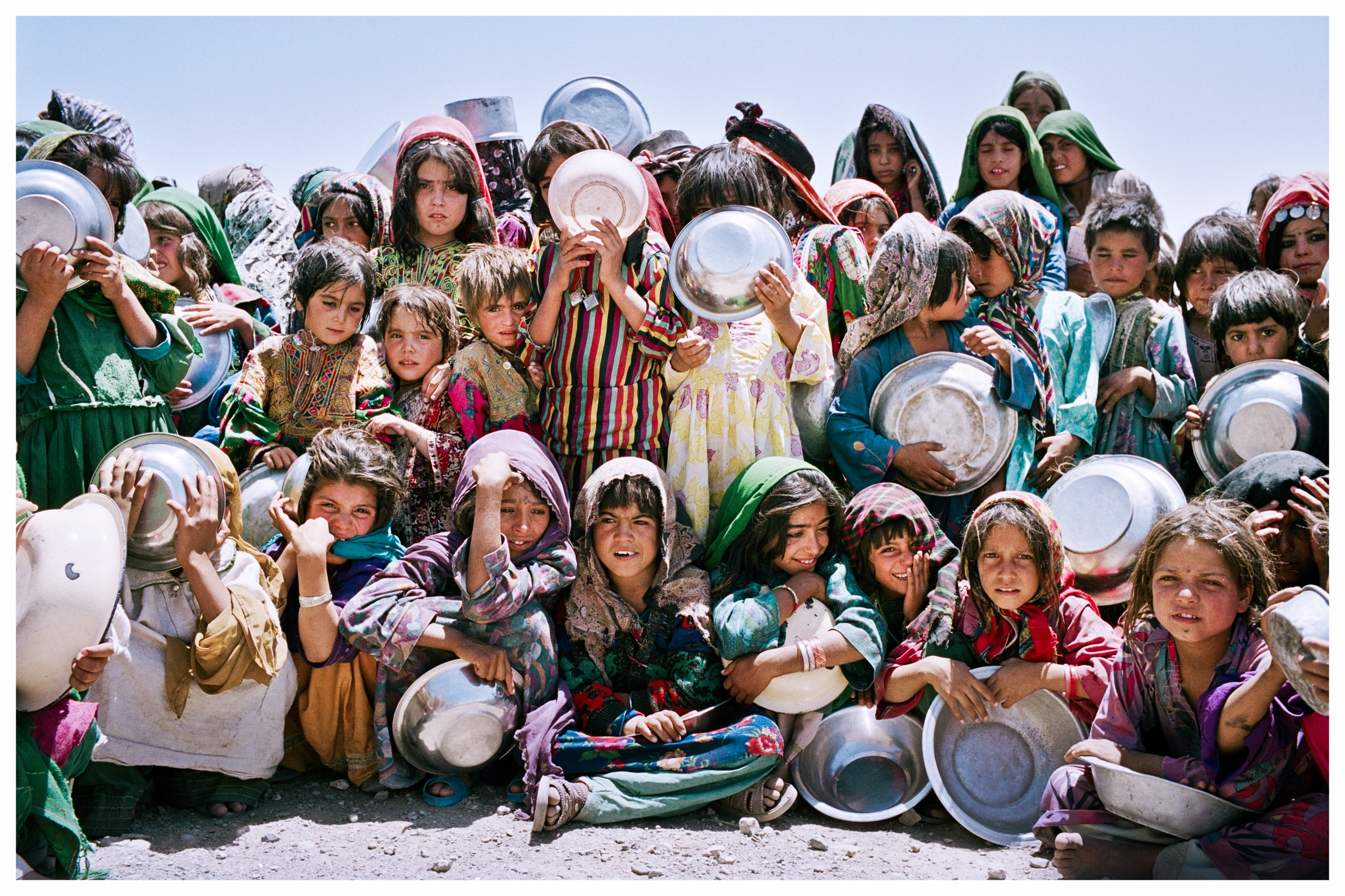 Afghan girls wait patiently in the mid-day heat to collect their ration of soup and bread.Western desert near Herat,Afghanistan. Photo © Marcus Perkins