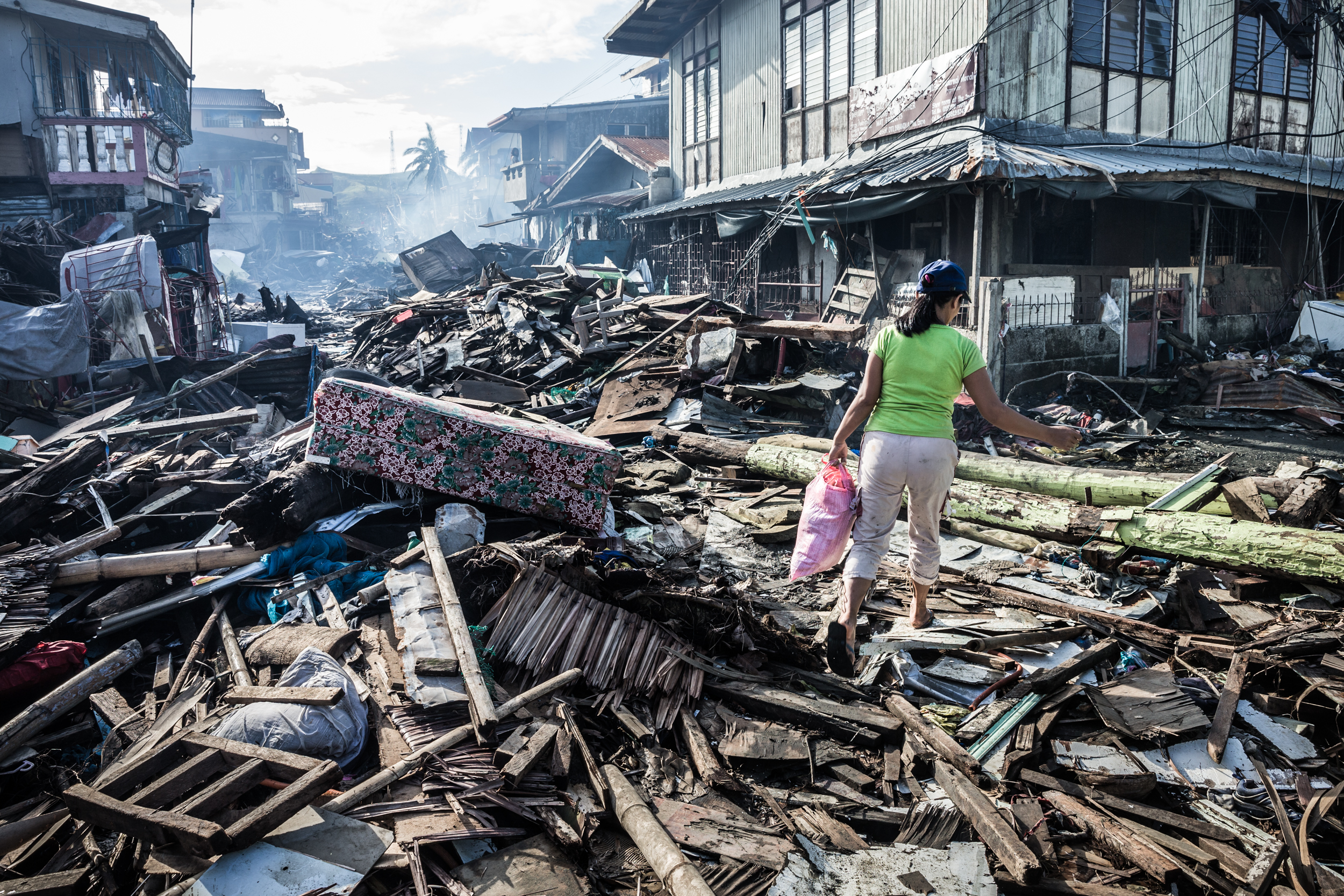 Treading carefully to avoid standing on hidden nails and other sharp objects, a woman picks her way through the main street of Basey. The town was destroyed after being hit by Typhoon Haiyan. Samar, Philippines.  Tearfund disaster response.