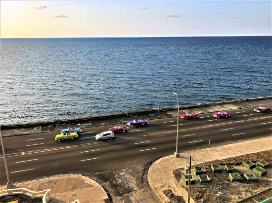 Catching the sunset in Havana as classic cars drive along the famous and historic Malecón