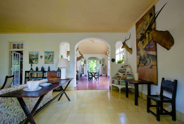 Sunlit interior hall of Hemingway's Cuban villa adorned with hunting trophies