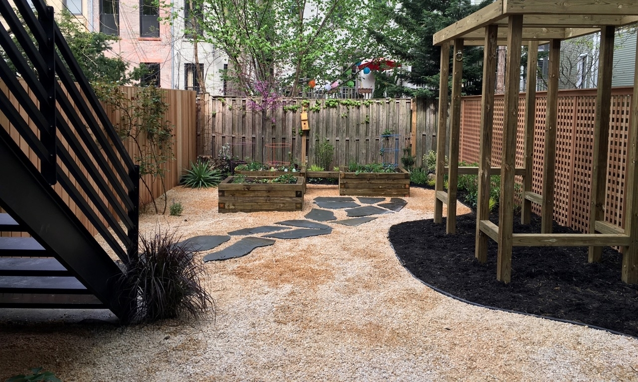Custom raised vegetable beds with seating that still leaves room for running around