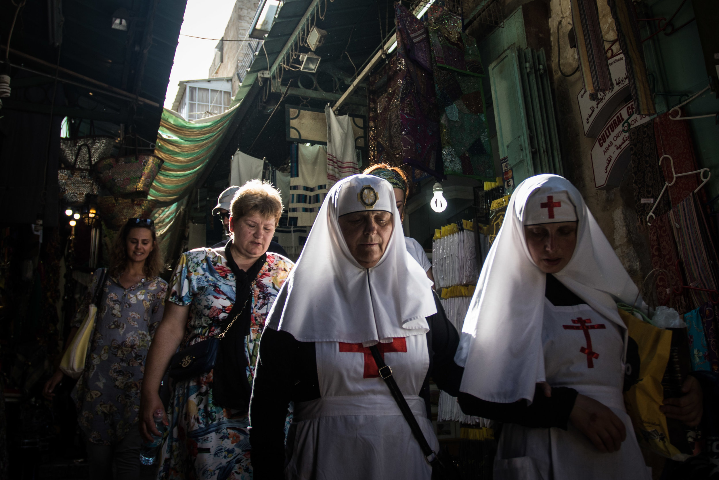 A pair of Christian nuns walk in front of a group of tourists through the alleyways of the Old City near merchandise shops with items designed to attract visitors of all faiths, July 12, 2016.
