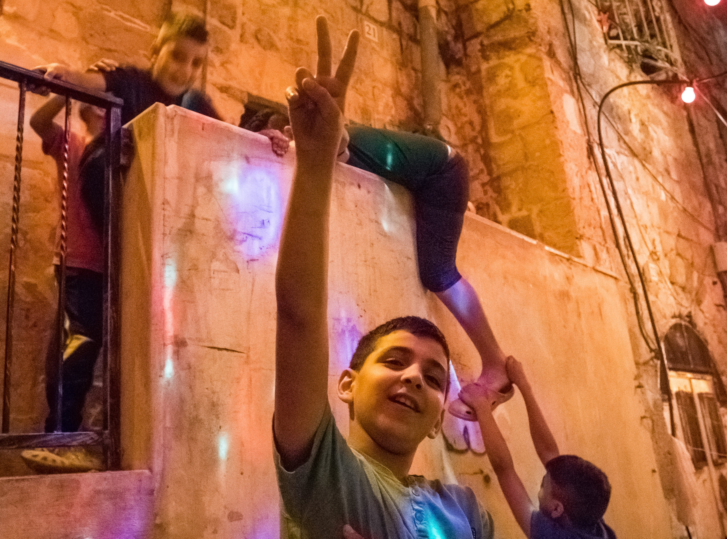 A group of Muslim boys clamor over each other to get their photo taken in an alleyway in the Old City at night during Ramadan celebrations, July 4, 2016.
