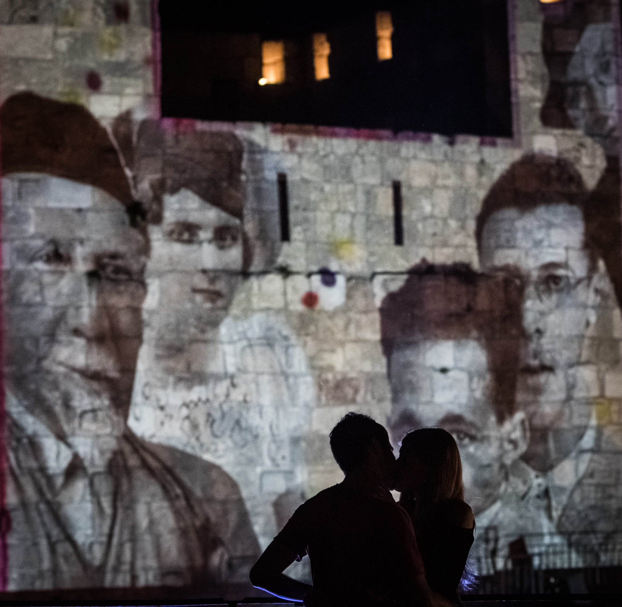 A couple shares an intimate moment in front of an artistic installation projected onto one of the ramparts inside the Tower of David museum as part of the Nylon  #2  art exhibition, July 7, 2016. The event featured dozens of live musicians, dance performances, live sketchings and other forms of art to celebrate the ending of the term for many of the city's local art students.