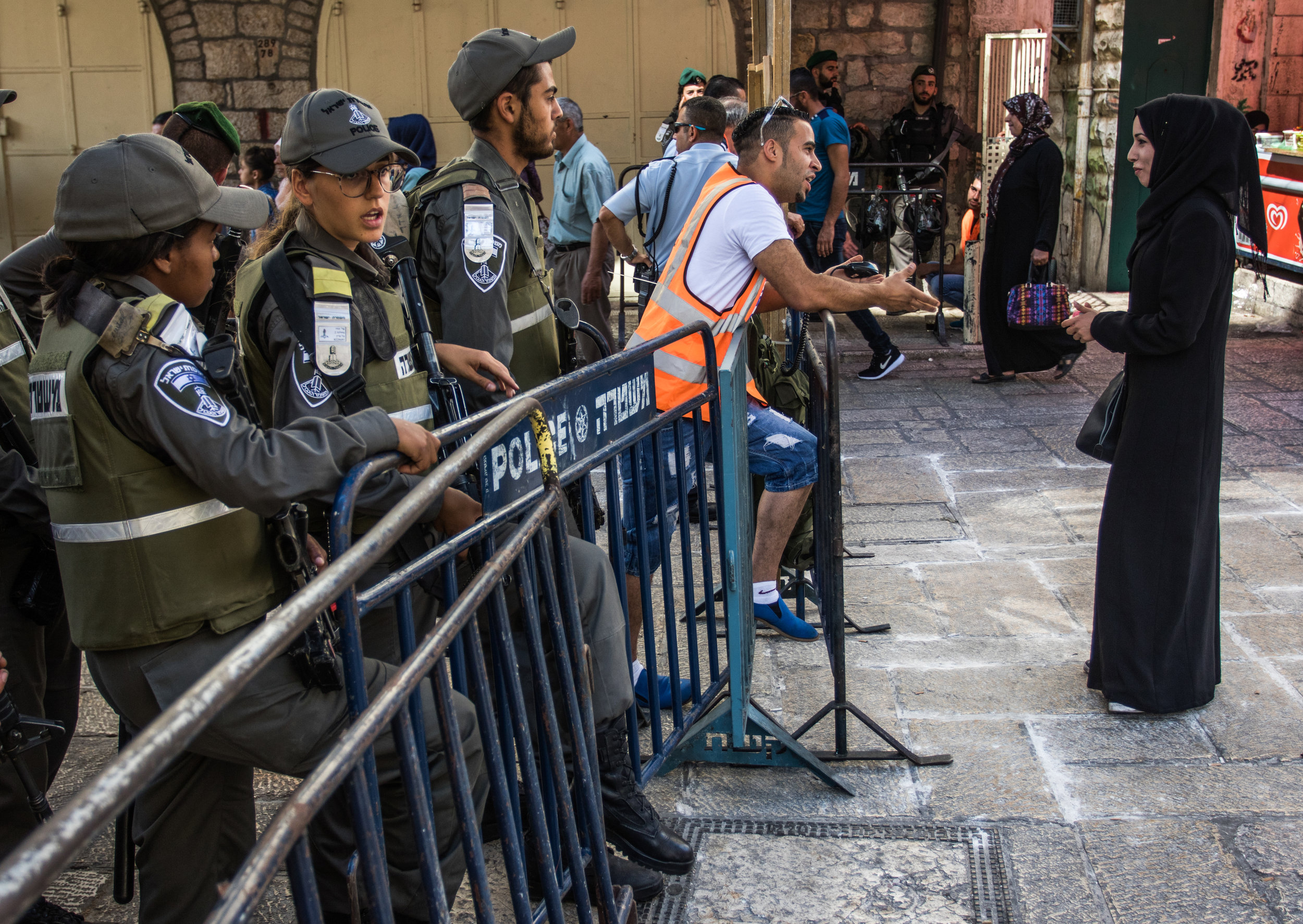 A Muslim woman stops to speak to a man directing Muslim worshippers toward the Al-Aqsa mosque for Friday Ramadan prayers in the Muslim quarter of the Old City, June 24, 2016. The security presence in the city was increased every Friday for the Muslim holy month due to the history of violent occurrences during the holiday.