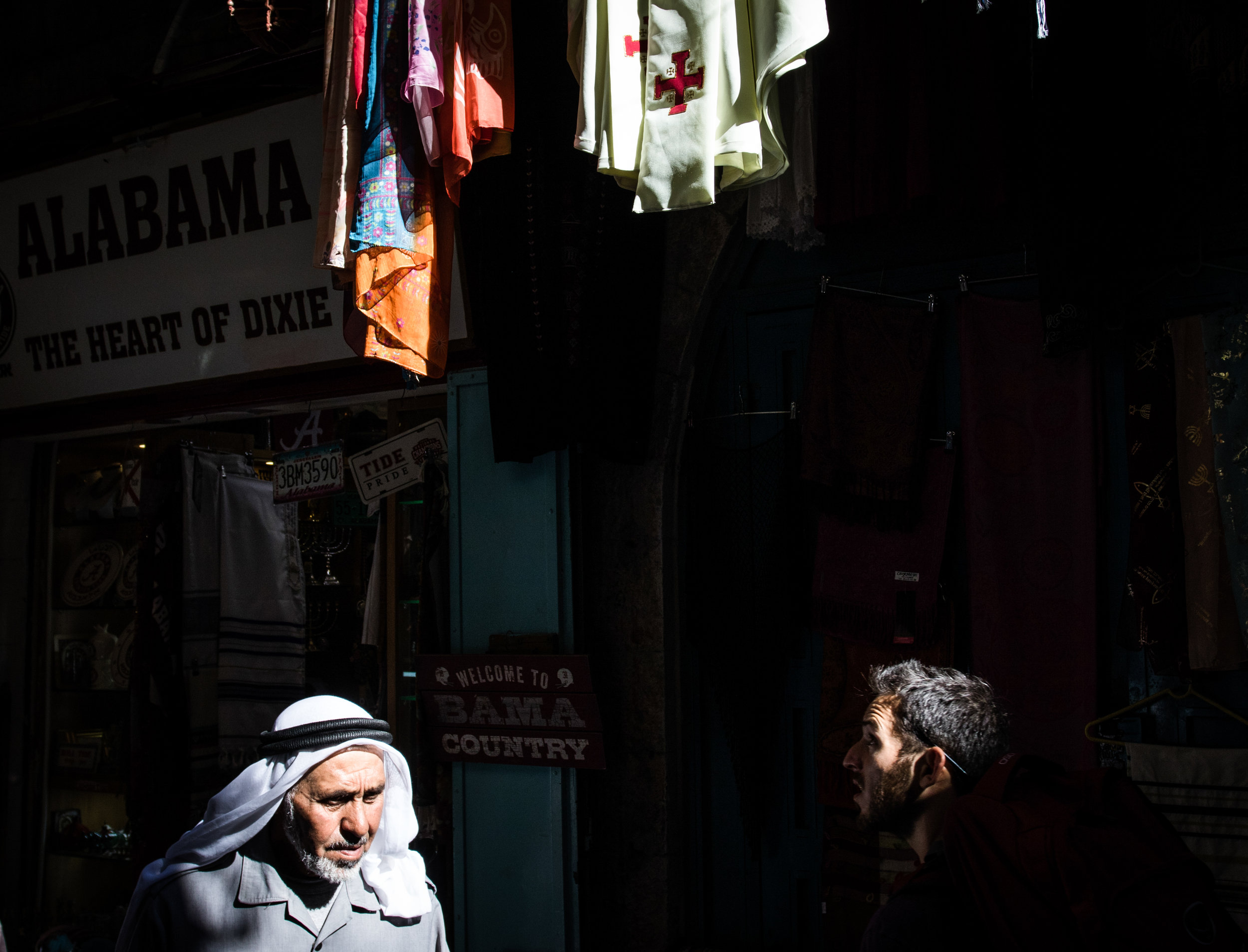 A Muslim man wearing a Keffiyeh passes under a set of scarves bearing the Christian cross on David Street in the Old City of Jerusalem, June 17, 2016.