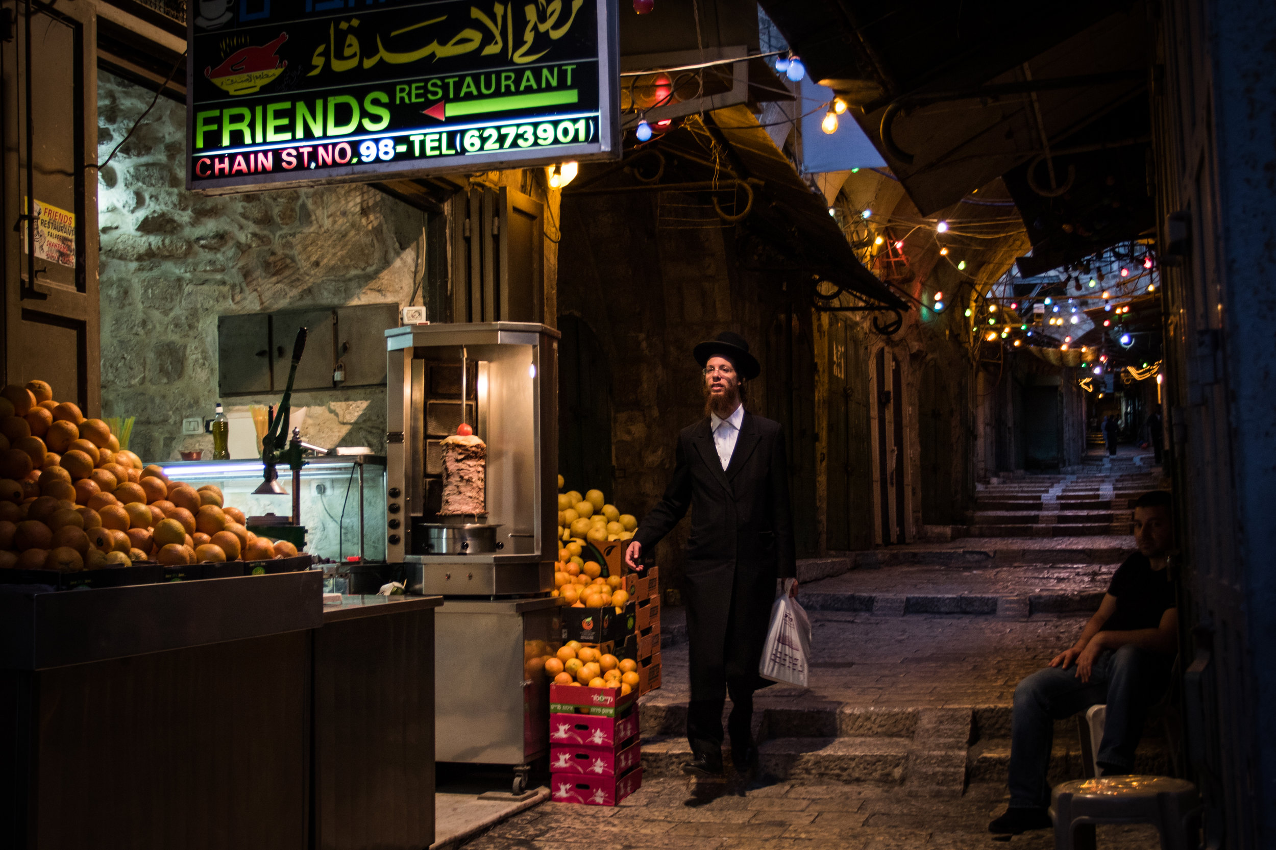 An Orthodox Jewish man makes his way through the empty streets of the Old City of Jerusalem towards the Western Wall under lights hung to celebrate the Muslim holiday of Ramadan, June 13, 2016.
