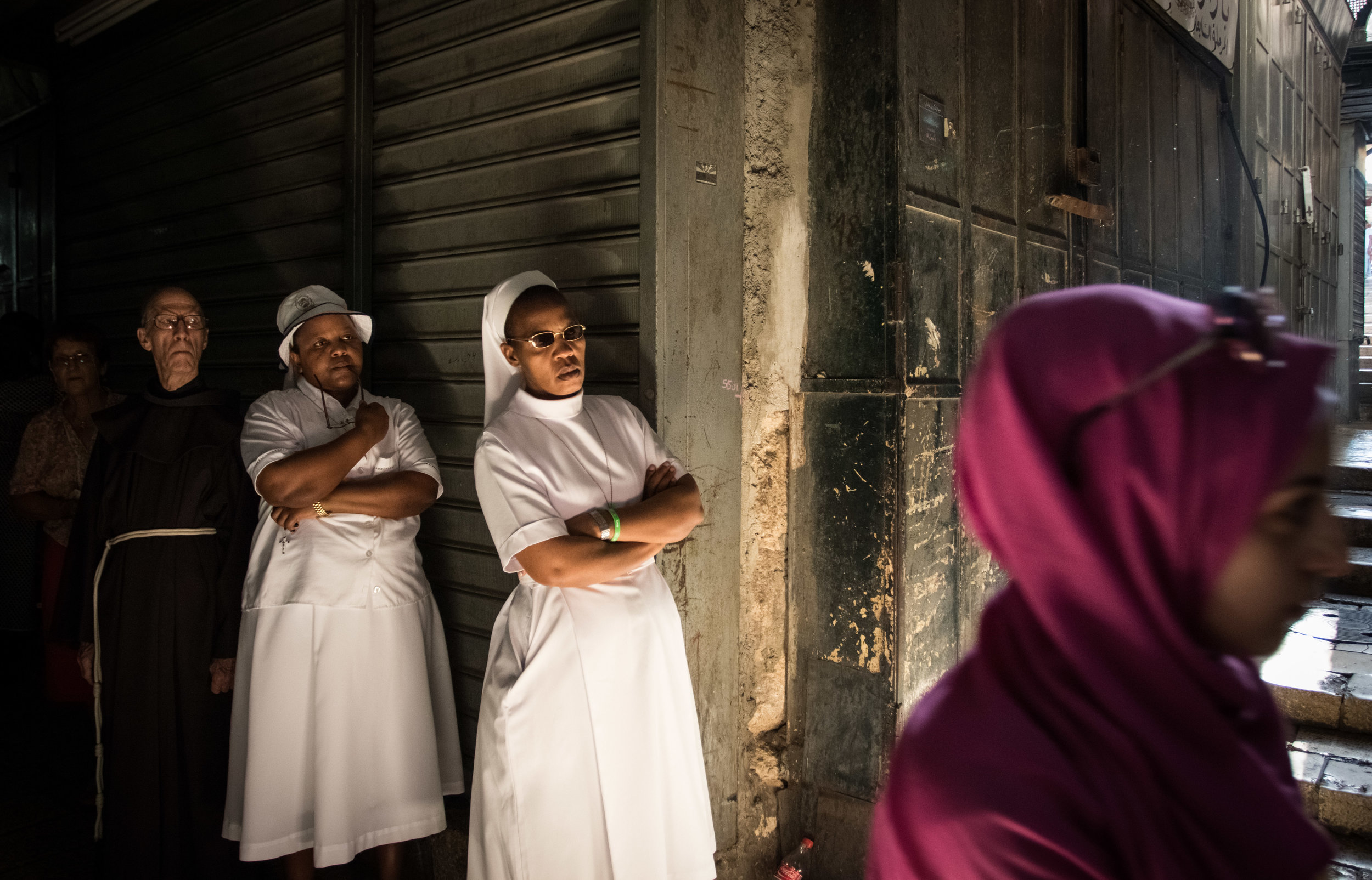 A Muslim woman passes by a group of Christian nuns and friars as they gather at one of the 15 stations of the cross during the weekly Way of the Cross walk through the Old City of Jerusalem, July 29, 2016. The path of the walk is believed to be the route Jesus Christ walked before being crucified by the Romans under the command of Pontius Pilate. Every Friday, a group of Christian worshippers begin walking from the Church of the Flagellation, near the first station of the cross, on Via Dolorosa, to the Holy Church of the Sepulchre, stopping along the way to pray at each of the stations where various events occurred during Jesus's crucifixion.