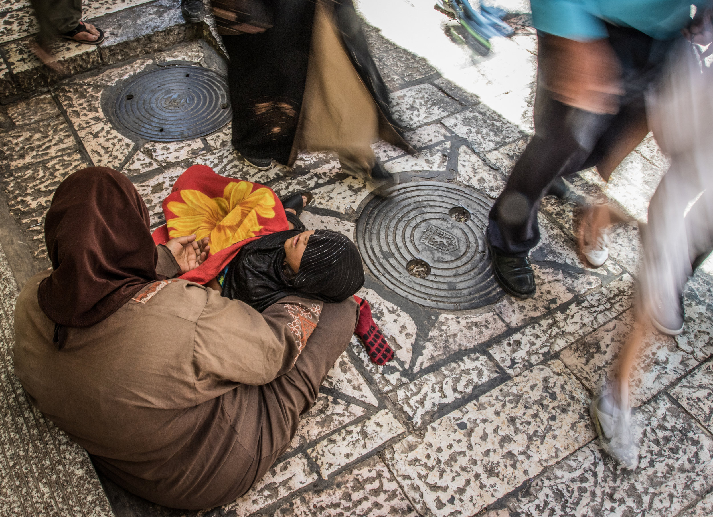 A woman asks for money from passersby as her child rests in her lap in the Old City of Jerusalem during the Islamic holy month of Ramadan, June 17, 2016. During the holy month, Muslims are encouraged to participate more heavily in Sadaqah, or voluntary charity and good works, as part of the religious celebrations.