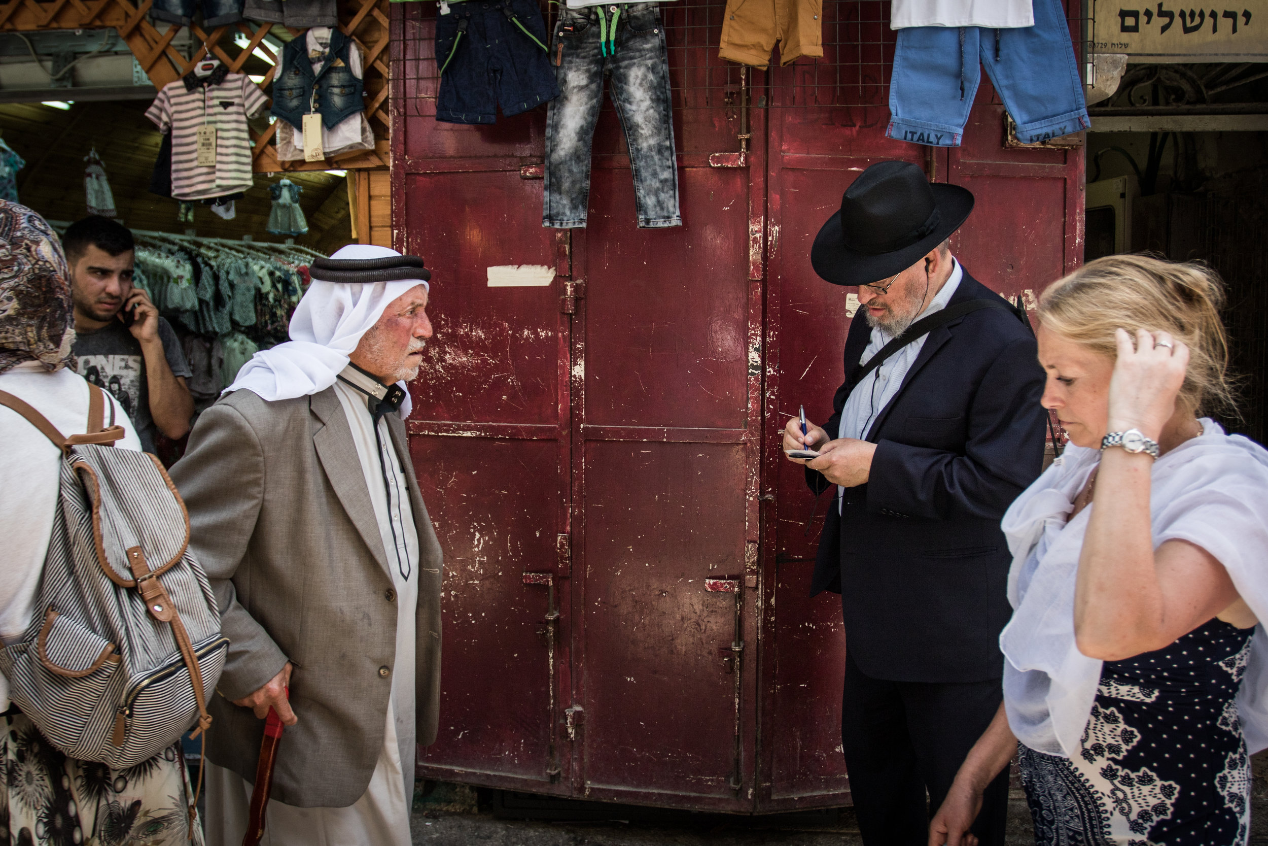 A Muslim man wearing a Keffiyeh passes by an Orthodox Jewish man in the Muslim quarter of the Old City near one of the many merchandise shops lining the streets, June 13, 2016.
