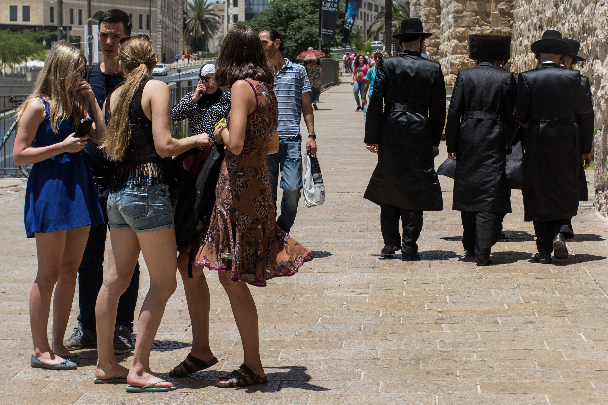 A group of Ultra-Orthodox Jewish men pass by a group of tourists outside of the Jaffa gate, the main tourist entrance into the Old City, June 13, 2016.