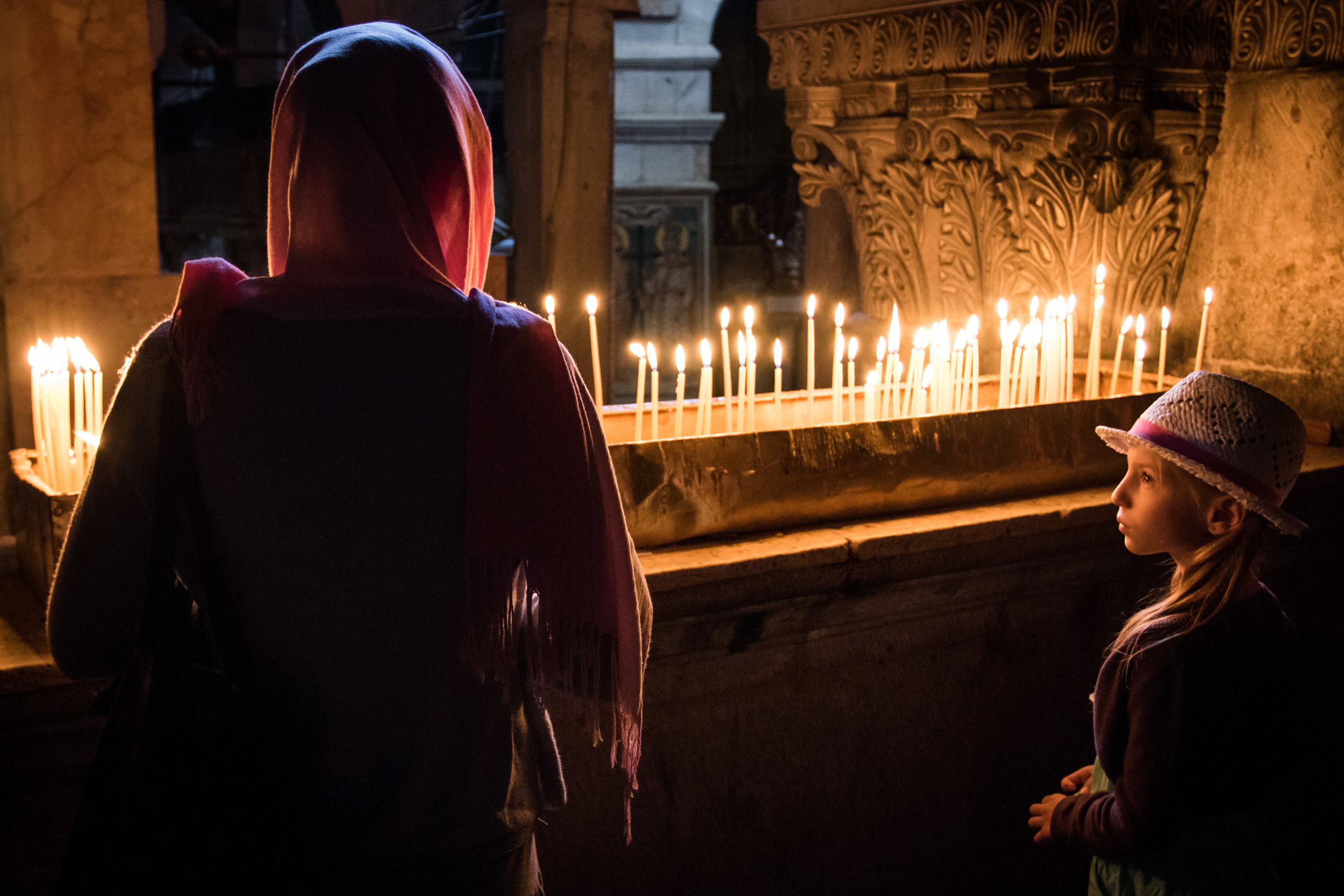 A young girl looks at a woman in a pink headdress near the candles at Calvary, the site where Jesus Christ was said to have been crucified inside the Church of the Holy Sepulchre in the Old City of Jerusalem, May 29, 2016.