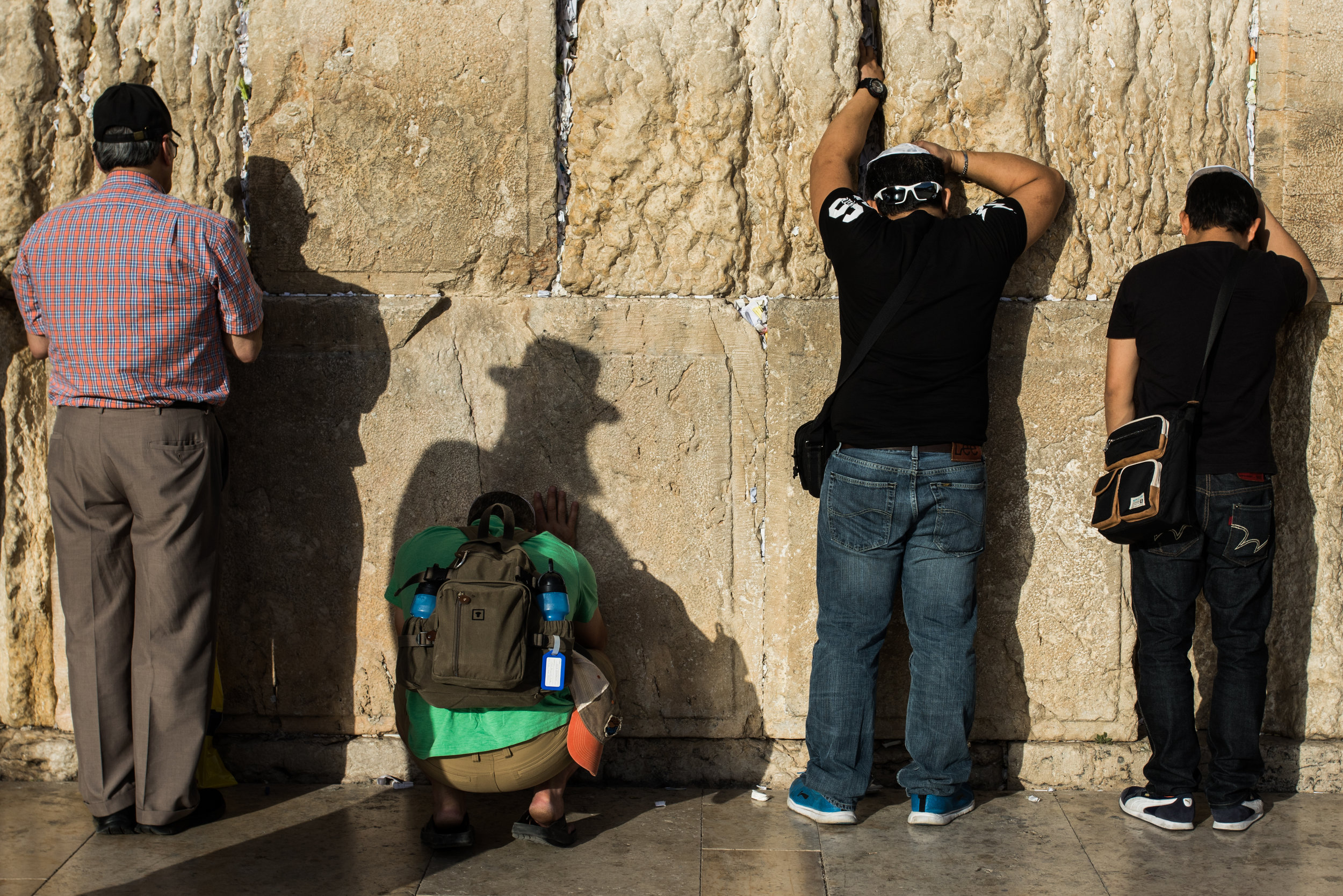 A group of men pray at the Western Wall, the most sacred monument where people are allowed to pray at in the Jewish religion, in the Old City of Jerusalem in the evening, June 7, 2016.