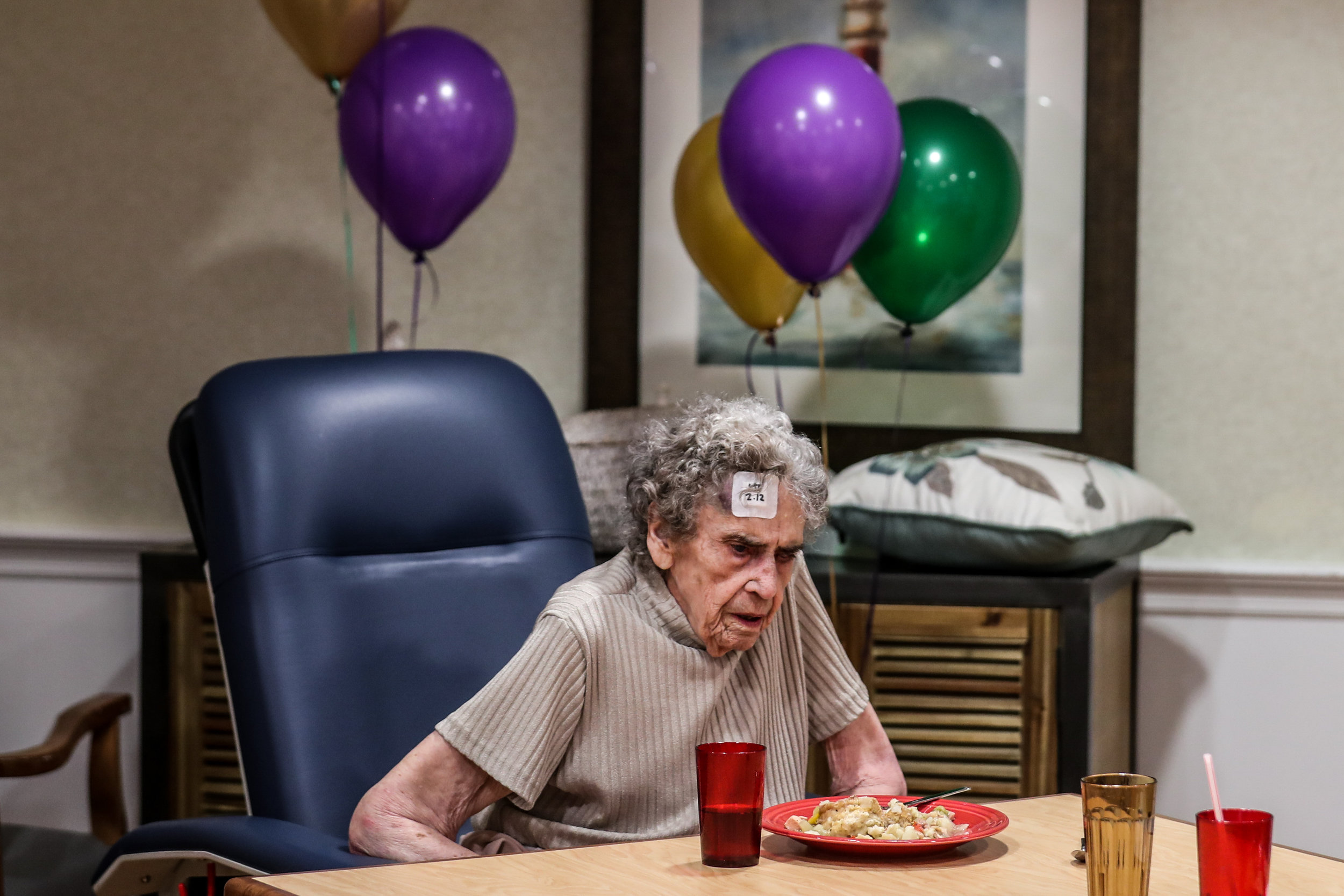 Mary King, 95, eats lunch at the RoseWood Village assisted living home on Greenbrier Drive during a Mardi Gras-themed meal. King, one of Lee Read's patients, died several days later.