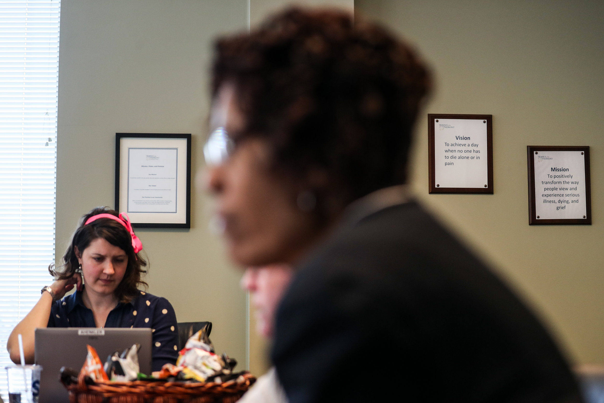 Hospice of the Piedmont staff sit during a team meeting at the organization's office near Martha Jefferson Hospital. Teams meet to discuss the status of each of their patients, what each patient needs and which patients have died since their last meeting.