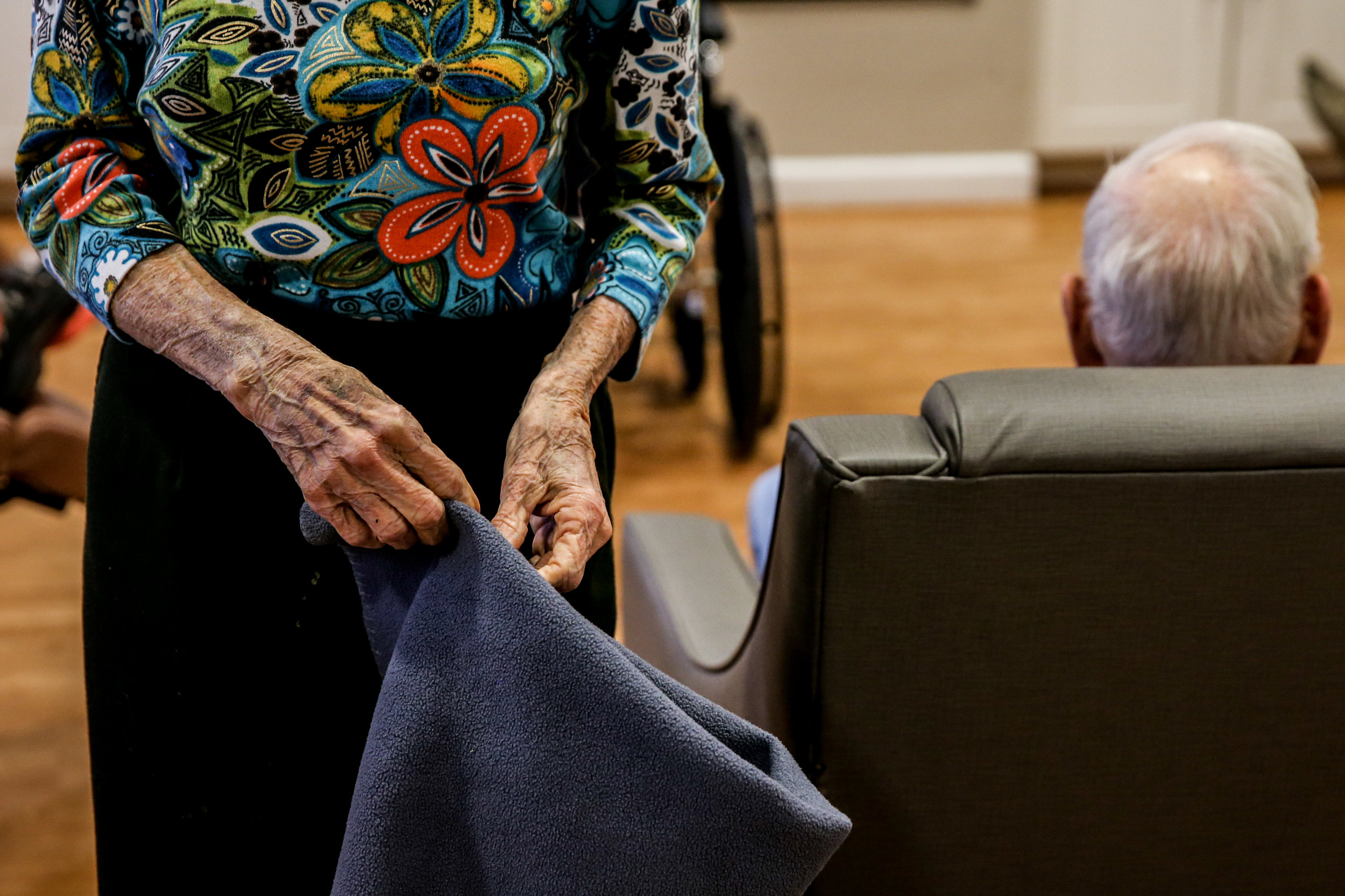 A patient tries to fold a blanket in the common area at the RoseWood Village assisted living home on Greenbrier Drive after lunch time. Many patients with dementia and alzheimer's retain small pieces of things they did earlier in life.