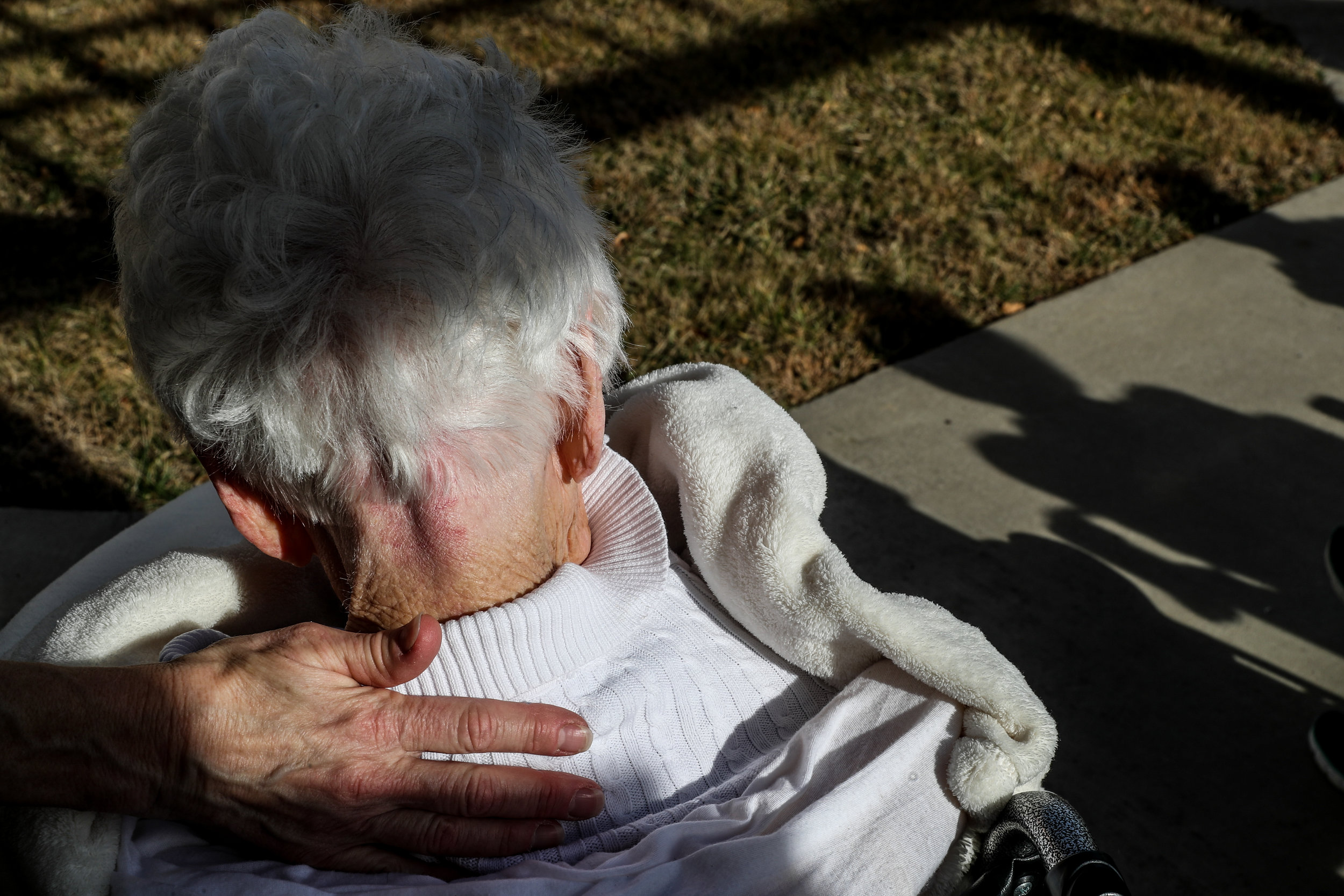 Lee Read rests her hand on Juanita Burke's, 97, neck as facility staff entertain patients outside on a sunny day at the RoseWood Village assisted living home at Hollymead Town Center. Burke, who had little strength left, died several days later.