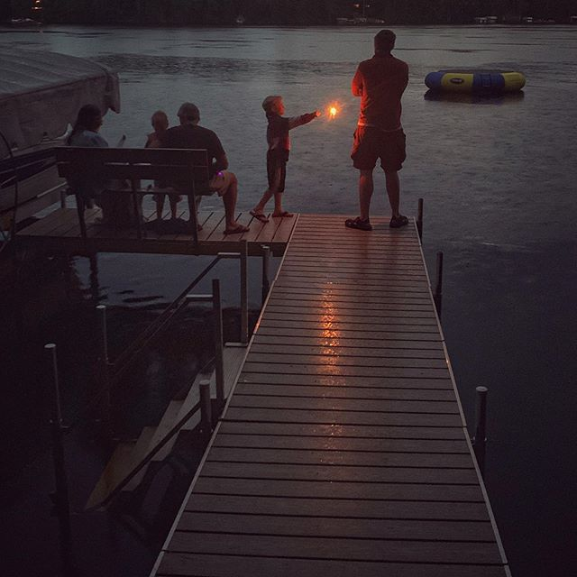 "A magical moment. A photo prompt if ever there was. . . ""Look Daddy,"" he says, standing on the dock in the flip flops he refuses to remove despite the blisters on the innocent flesh between his toes, because big boys wear flip flops. Big boys don't need heel straps. They need callouses. . . ""Look Daddy,"" he says, pointing a sharp stick of fire. ""Spell your name,"" I yell from behind the camera. He doesn't hear me. And later, when he does, he's not interested. He has a flaming stick, he's not interested in cursive. . . ""Look Daddy,"" he says, and I have to hope he never stops asking us to look. . . #sparklers #4thofjuly #magicalmoment #raisingboys #lakehousemagic #makeshiftgenius #amwriting #summerwriting"